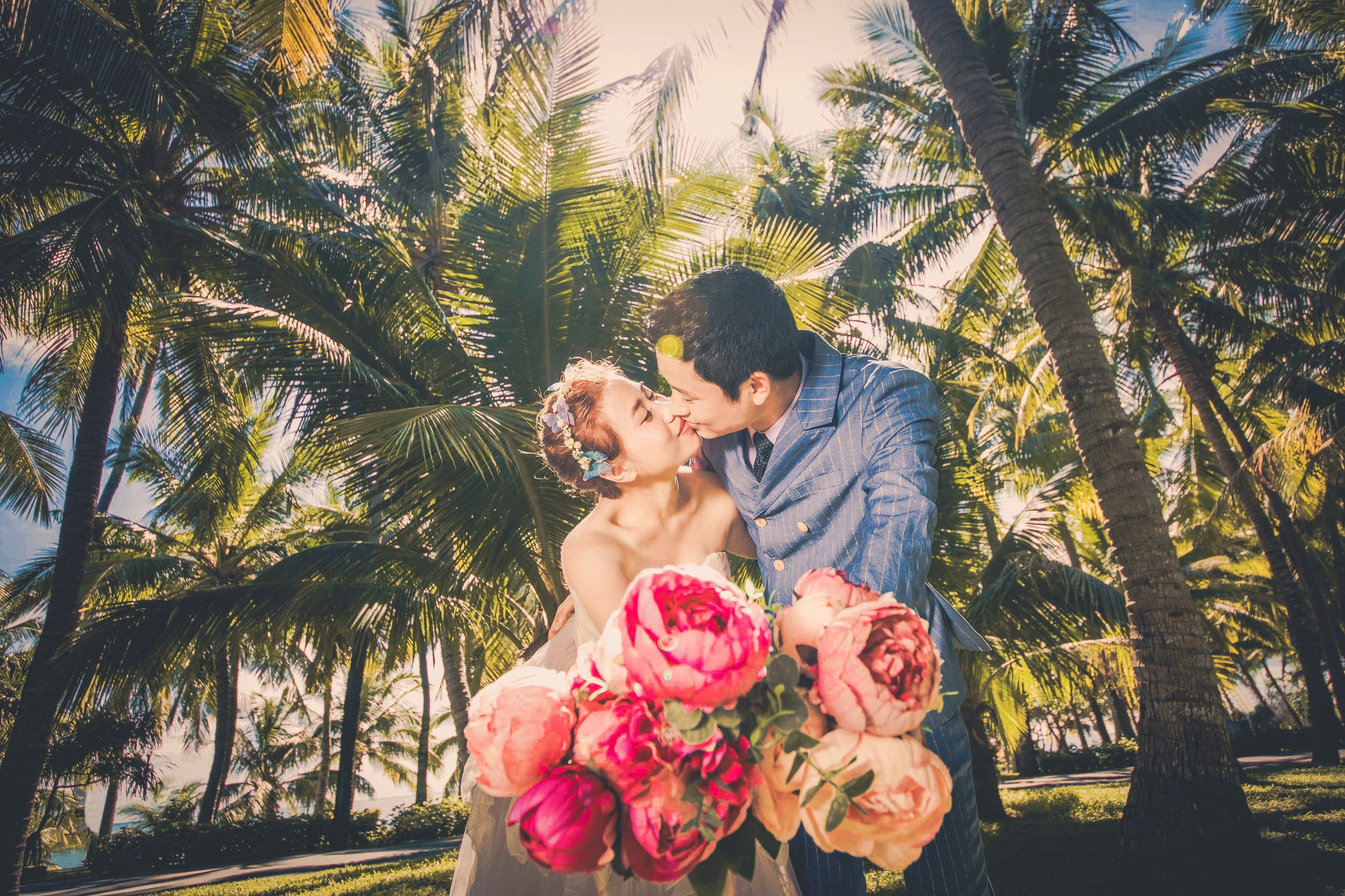 palm tree, young women, tree, young adult, leisure activity, growth, flower, pink color, lifestyles, person, casual clothing, leaf, eyes closed, nature, beauty in nature, tree trunk, fragility, human face, rose - flower, green color, day, outdoors, red, freshness