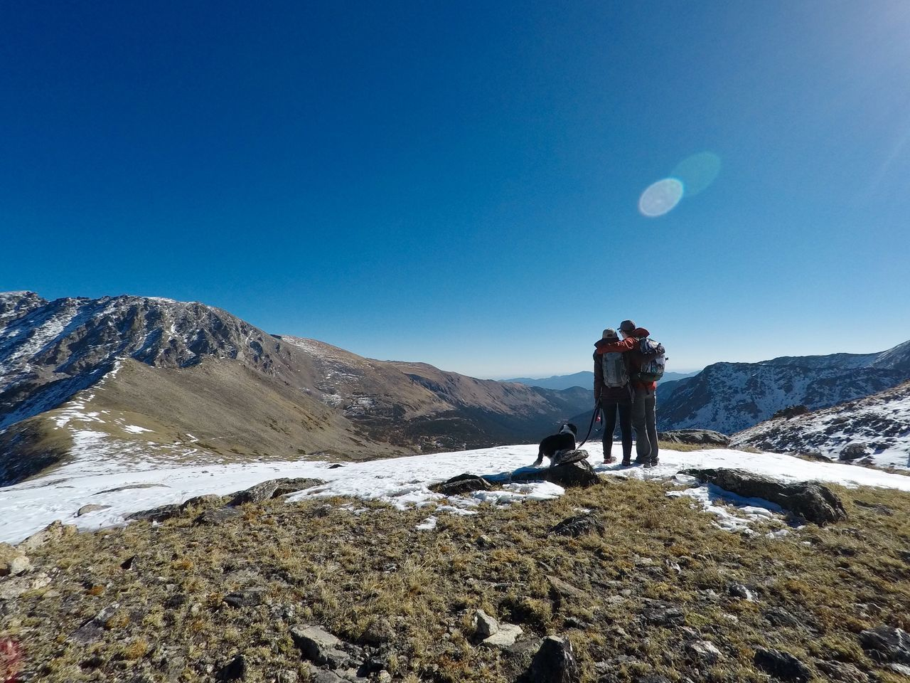 Rear View Of Hikers With Dog Standing On Rocky Mountain Against Blue Sky