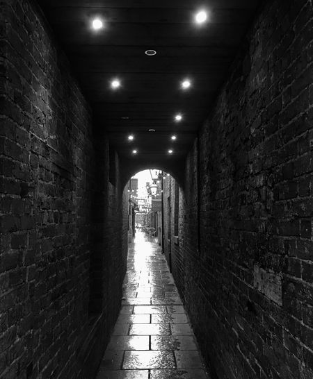 Down an alley.... Illuminated The Way Forward Architecture Indoors  Brick Wall Long Built Structure Tunnel One Person Passage Day Oswestry Blackandwhite Photography Black & White IPhone SE IPhone Photography IPhoneography Historic Rainy Days Outdoors Architecture Iphoneonly
