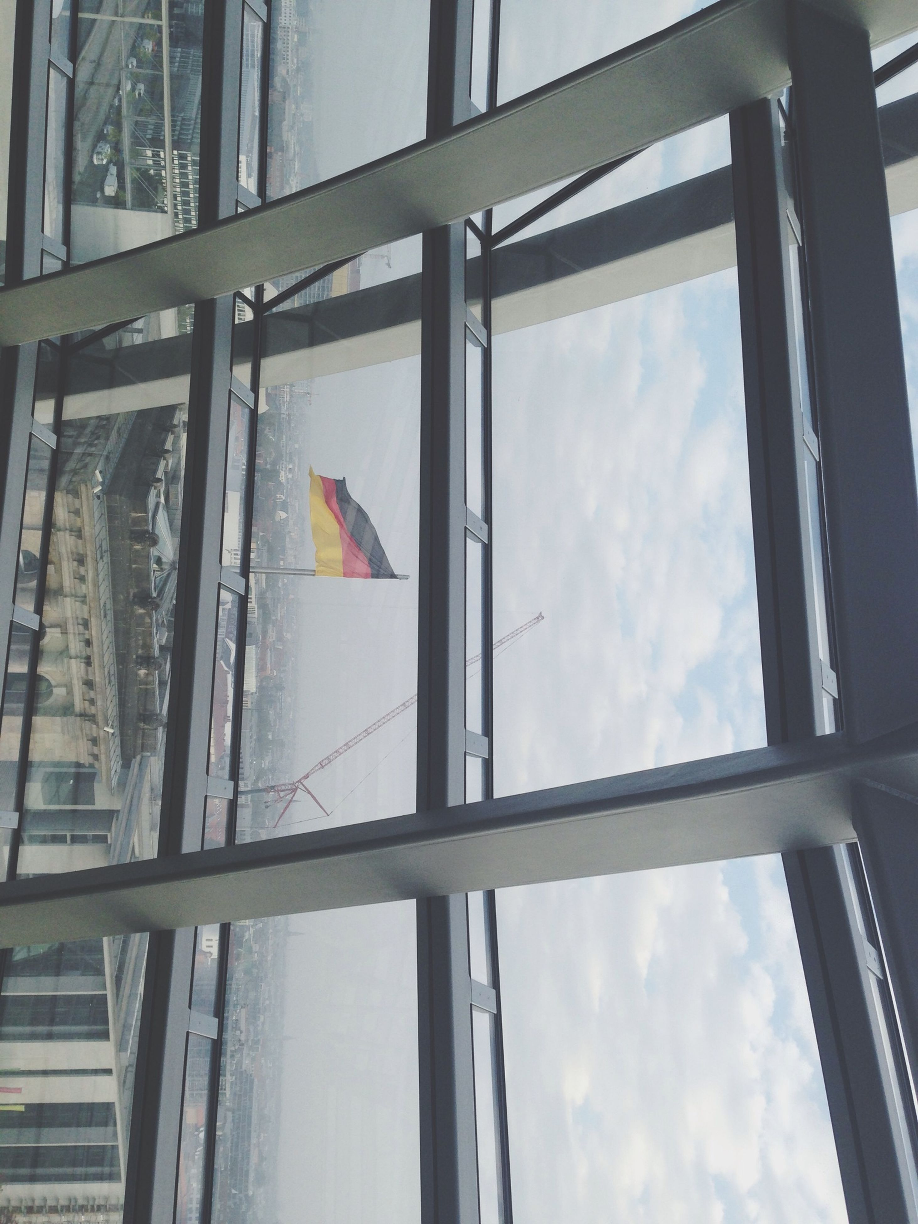 architecture, built structure, low angle view, window, glass - material, building exterior, sky, cloud - sky, transparent, building, day, city, cloud, indoors, reflection, cloudy, no people, glass, modern