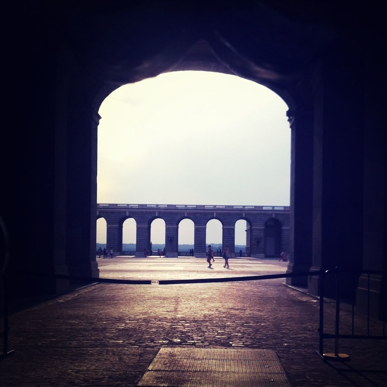 Empty walkway with arched wall against sea and sky