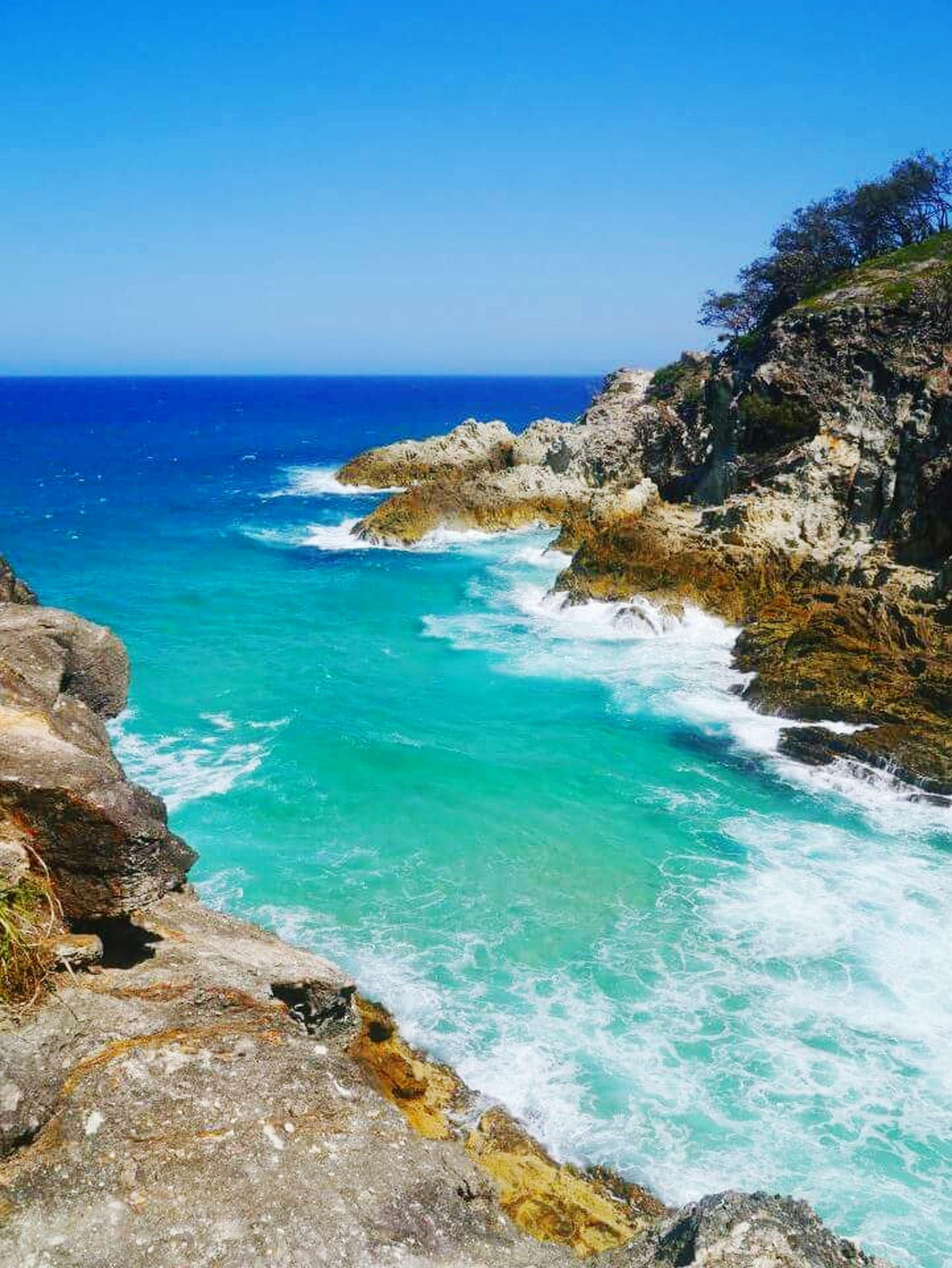 sea, water, horizon over water, blue, clear sky, scenics, tranquil scene, beauty in nature, rock - object, tranquility, rock formation, nature, rock, copy space, idyllic, cliff, coastline, shore, day, sky