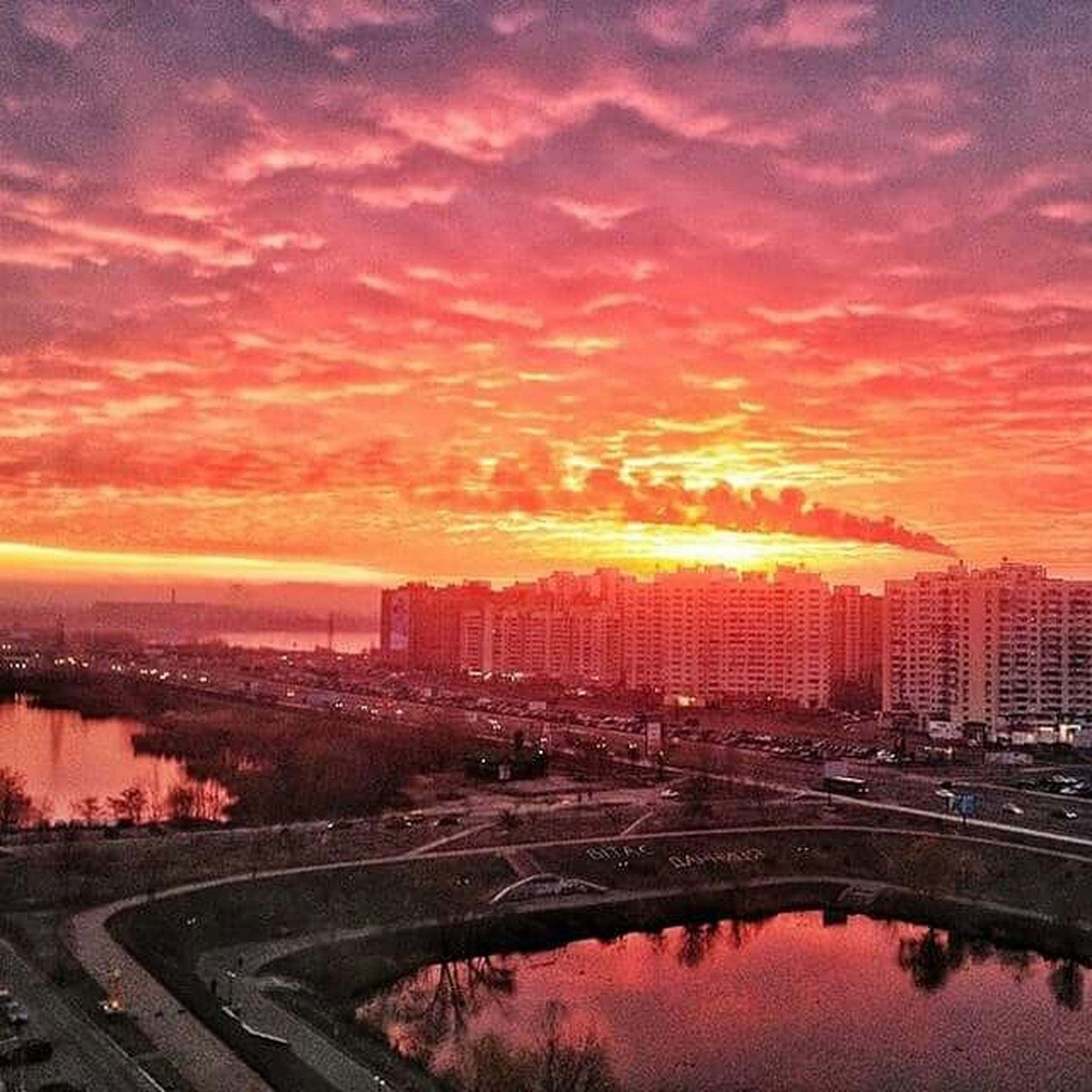 sunset, architecture, sky, built structure, cloud - sky, building exterior, city, orange color, cityscape, high angle view, dramatic sky, cloudy, cloud, illuminated, dusk, outdoors, water, connection, city life, river