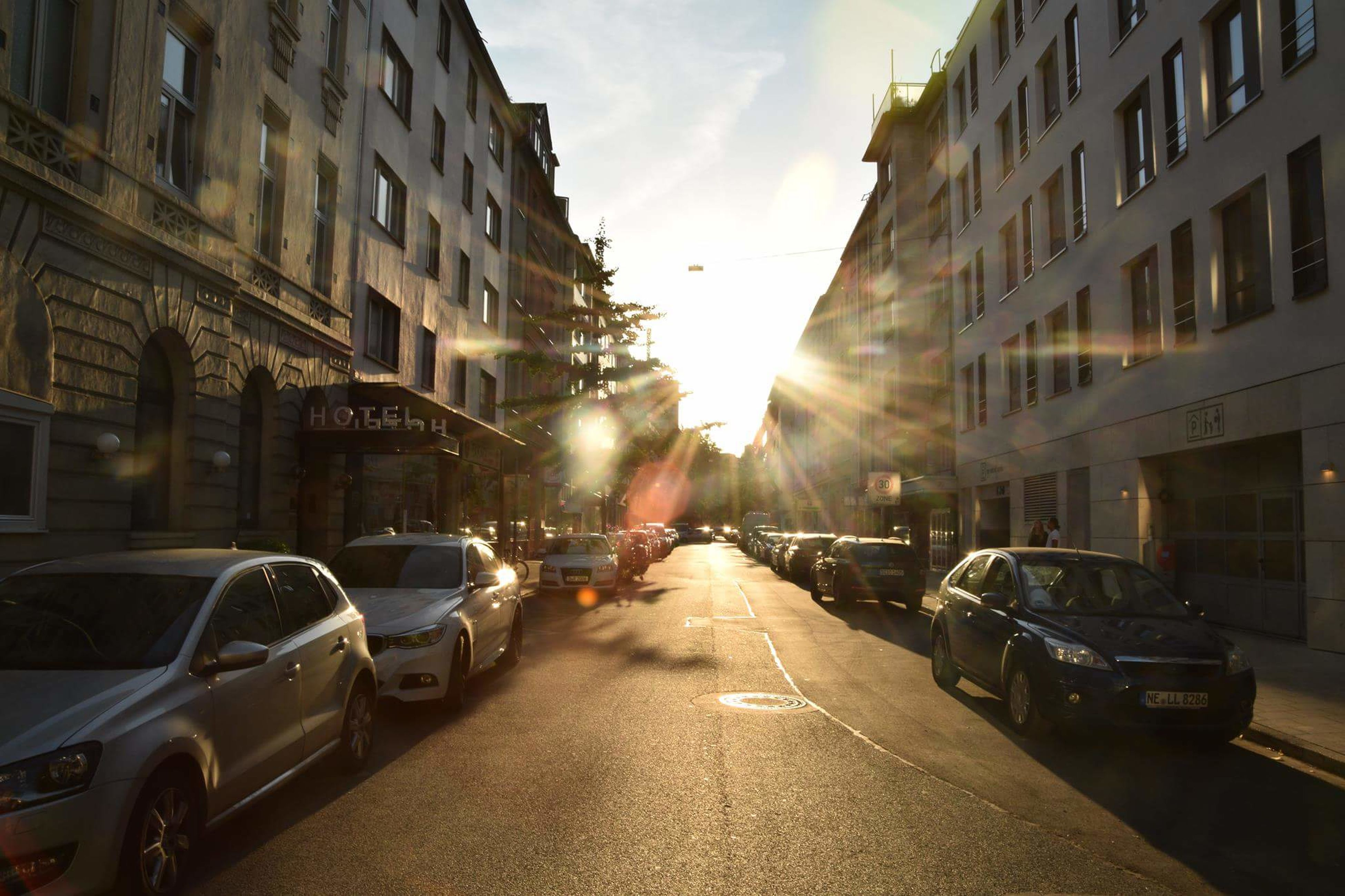 car, street, architecture, building exterior, transportation, city, built structure, sunlight, land vehicle, road, mode of transport, sunset, sky, outdoors, no people, day
