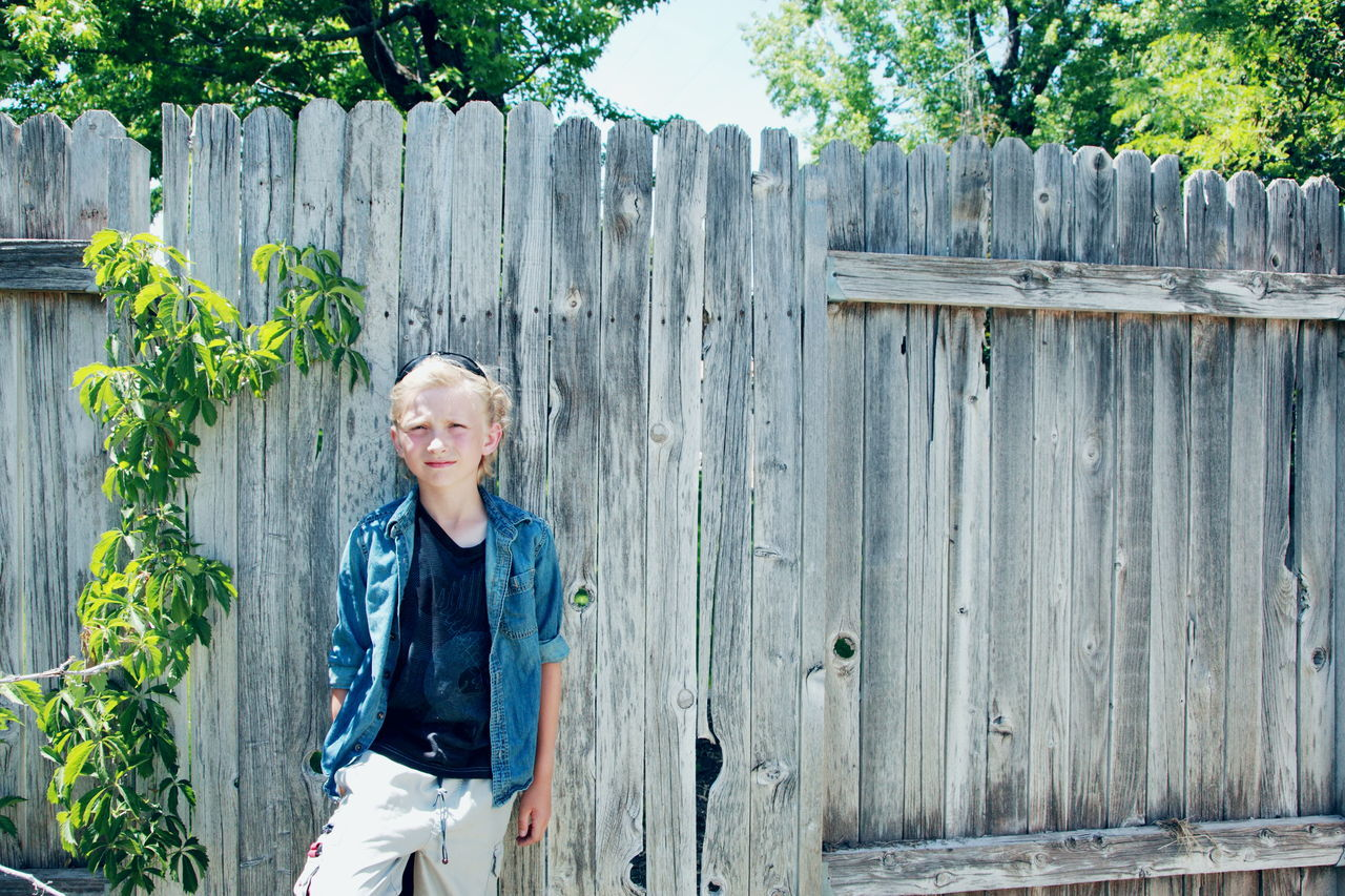 Portrait Of Smiling Boy Standing Against Fence