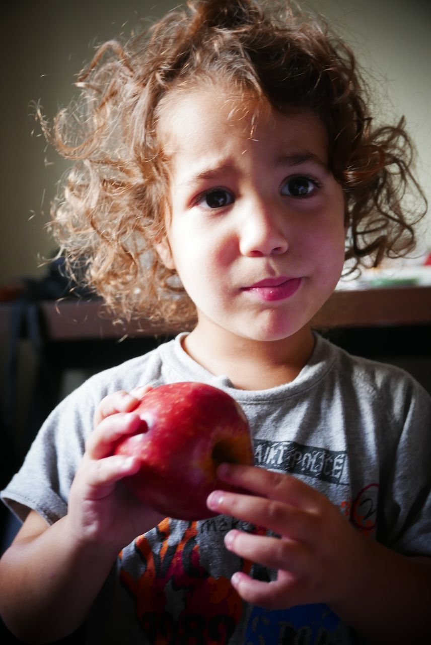 Close-Up Of Cute Boy Holding Apple At Home