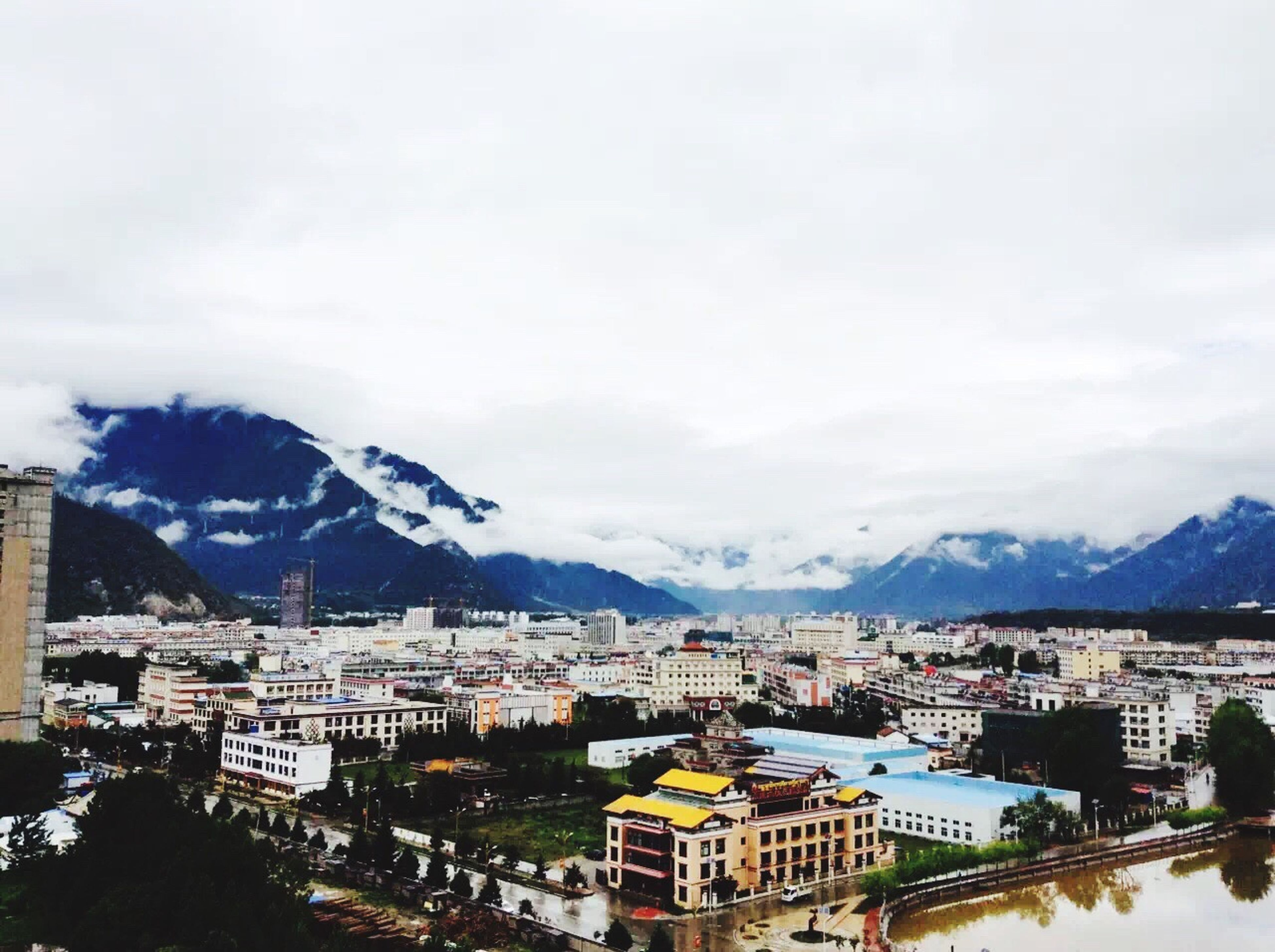 mountain, building exterior, architecture, built structure, mountain range, sky, residential district, house, city, cityscape, town, residential structure, residential building, cloud - sky, high angle view, townscape, winter, crowded, cloud, weather