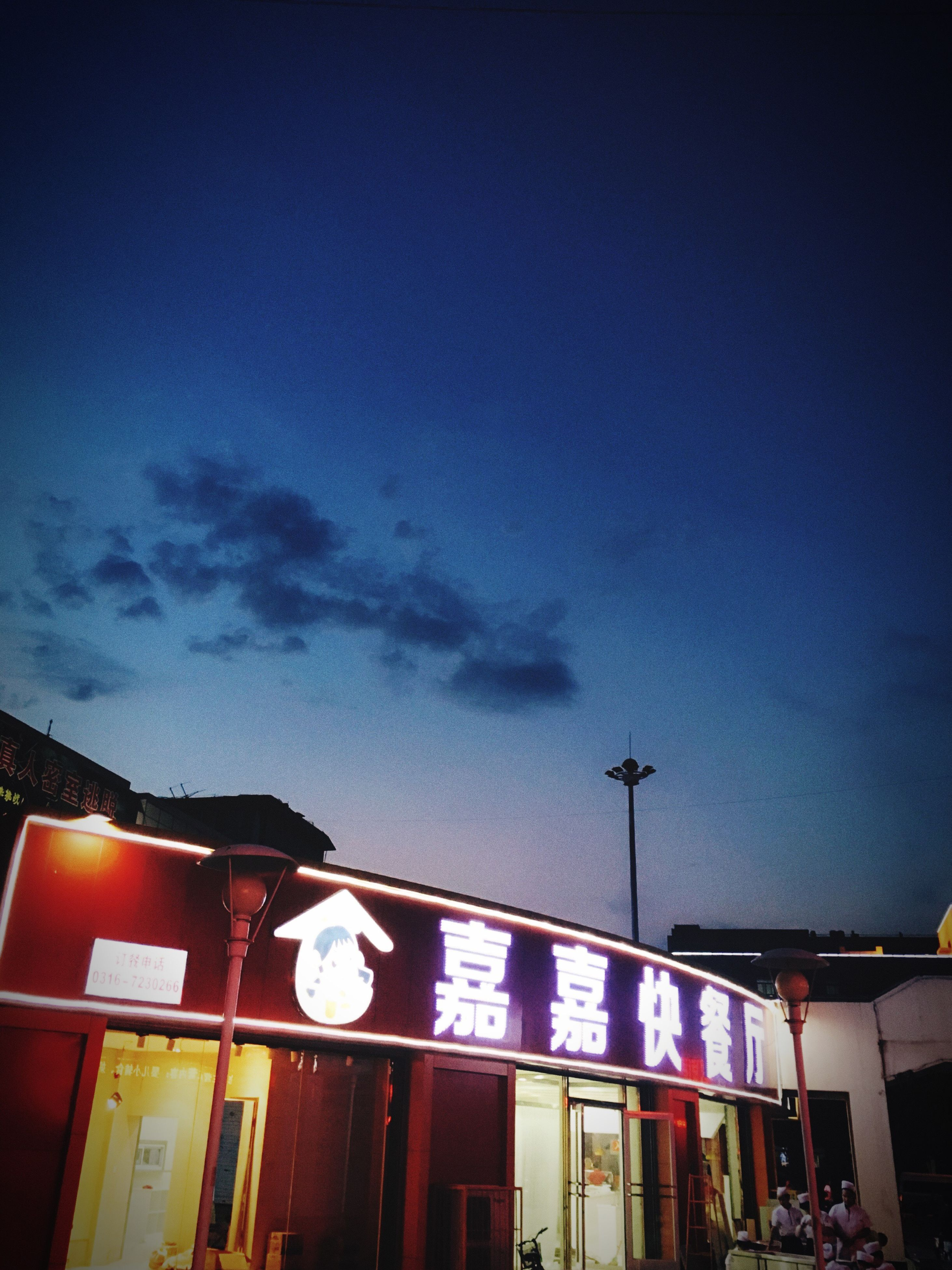low angle view, built structure, architecture, sky, building exterior, illuminated, night, street light, lighting equipment, dusk, cloud - sky, city, building, outdoors, text, transportation, blue, cloud, no people, communication