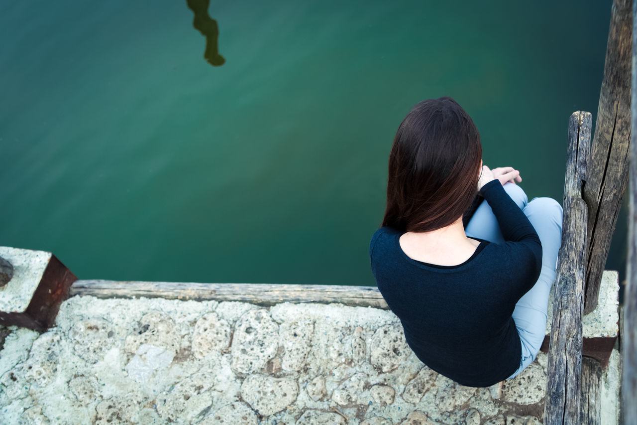 Rear View Of Young Woman Sitting On Pier By Lake