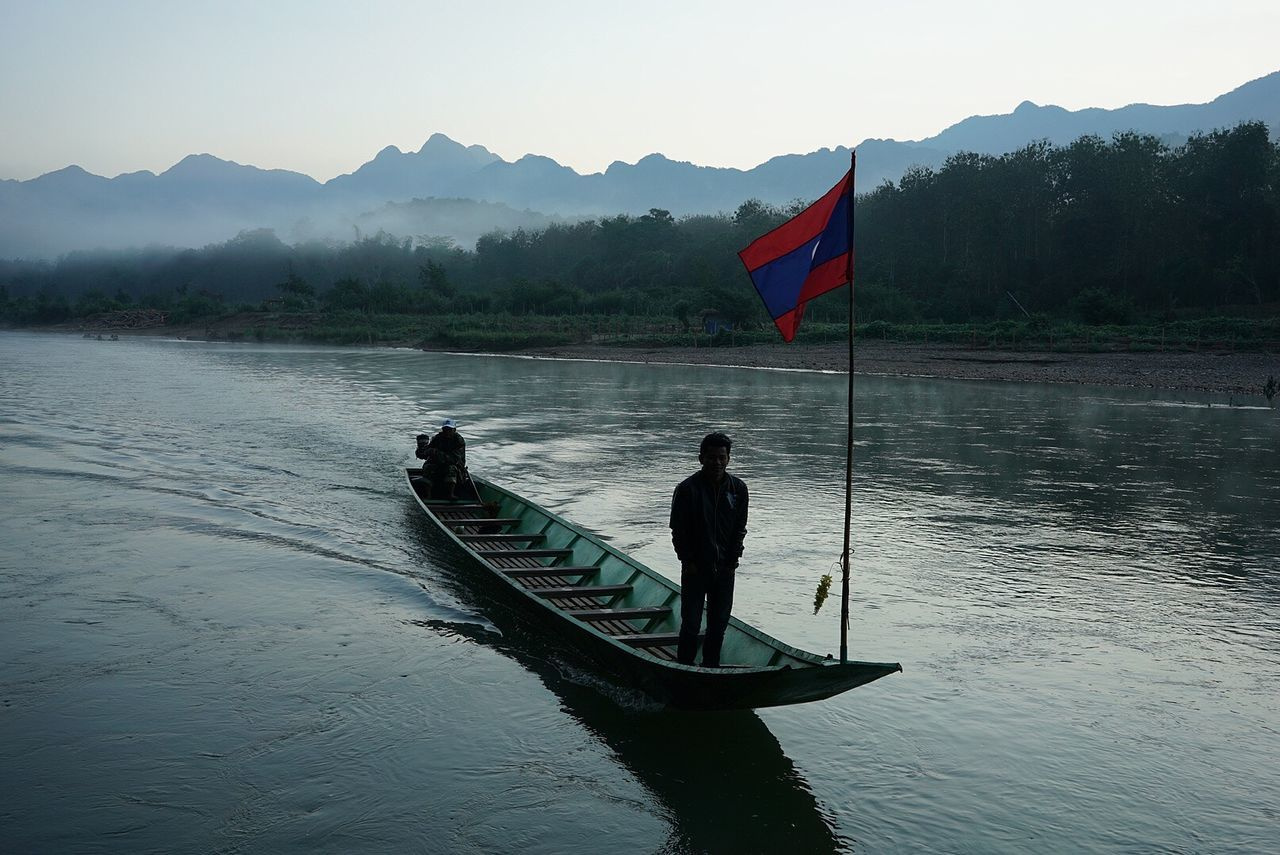 Adult Adventure Beauty In Nature Clear Sky Day Flag Fog Jungle Landscape Laos Men Mountain Nature Nautical Vessel One Person Outdoors Patriotism People Real People River River View Sky Travel Photography Water