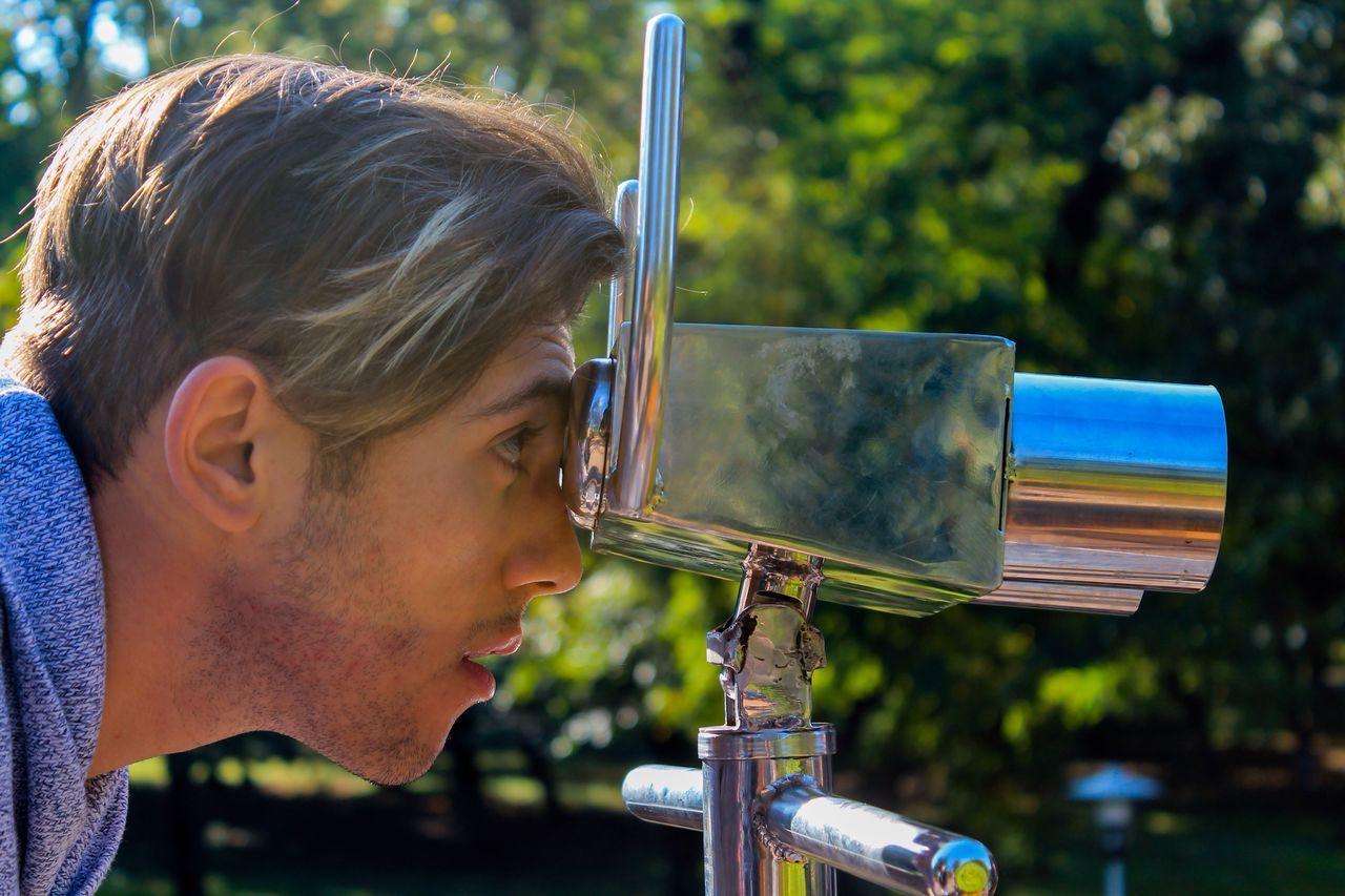 Close-Up Of A Man Looking Through Binoculars Outdoors
