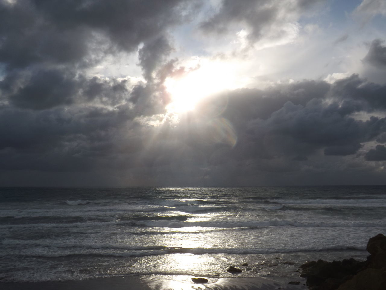 sea, sunbeam, horizon over water, beauty in nature, scenics, sunlight, nature, cloud - sky, sky, water, tranquility, tranquil scene, lens flare, sun, idyllic, outdoors, reflection, no people, wave, day, sunset, beach, storm cloud