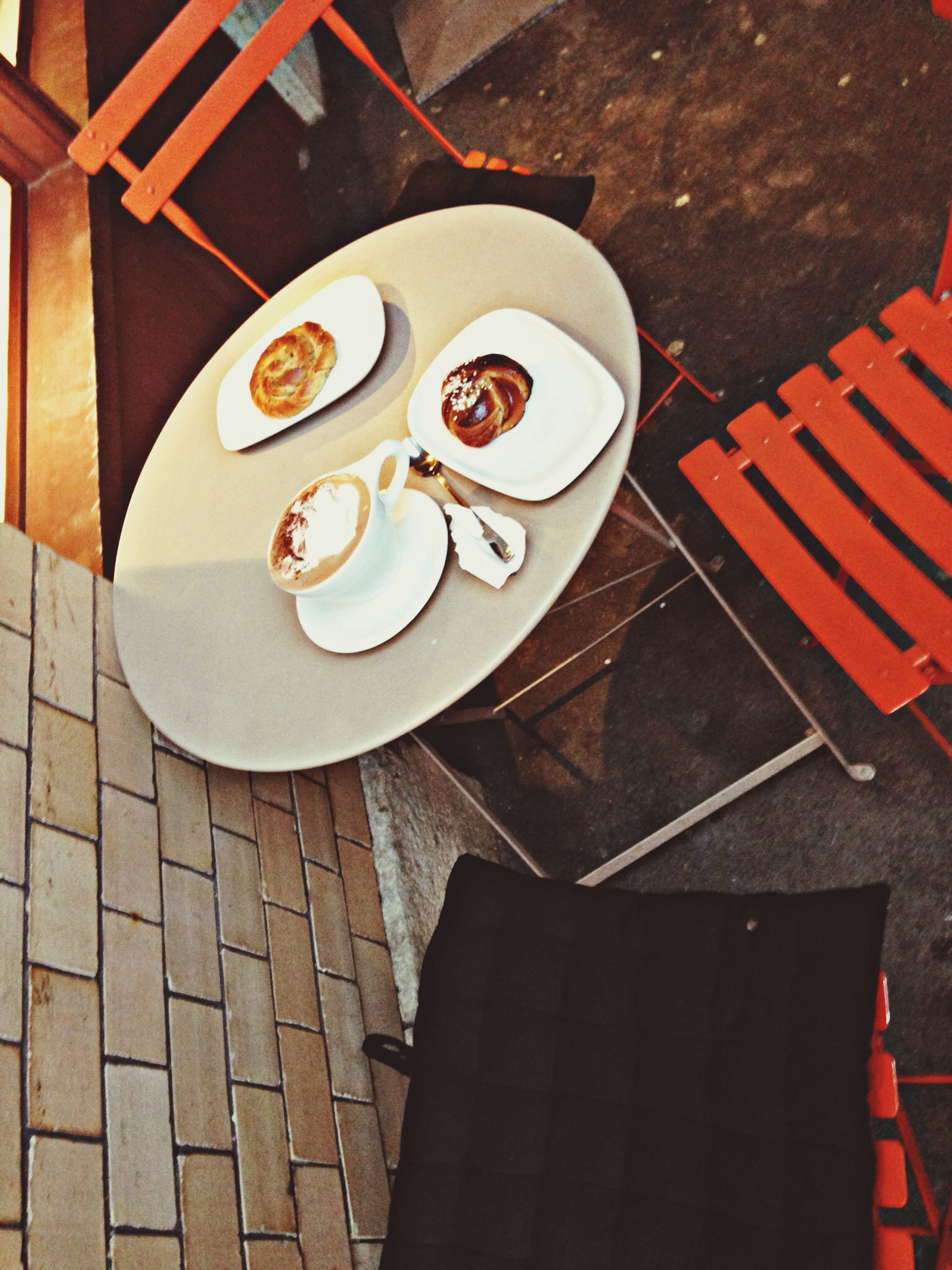 high angle view, table, indoors, directly above, day, still life, shadow, sidewalk, no people, communication, elevated view, street, pattern, red, close-up, sunlight, coffee cup, cobblestone, tiled floor
