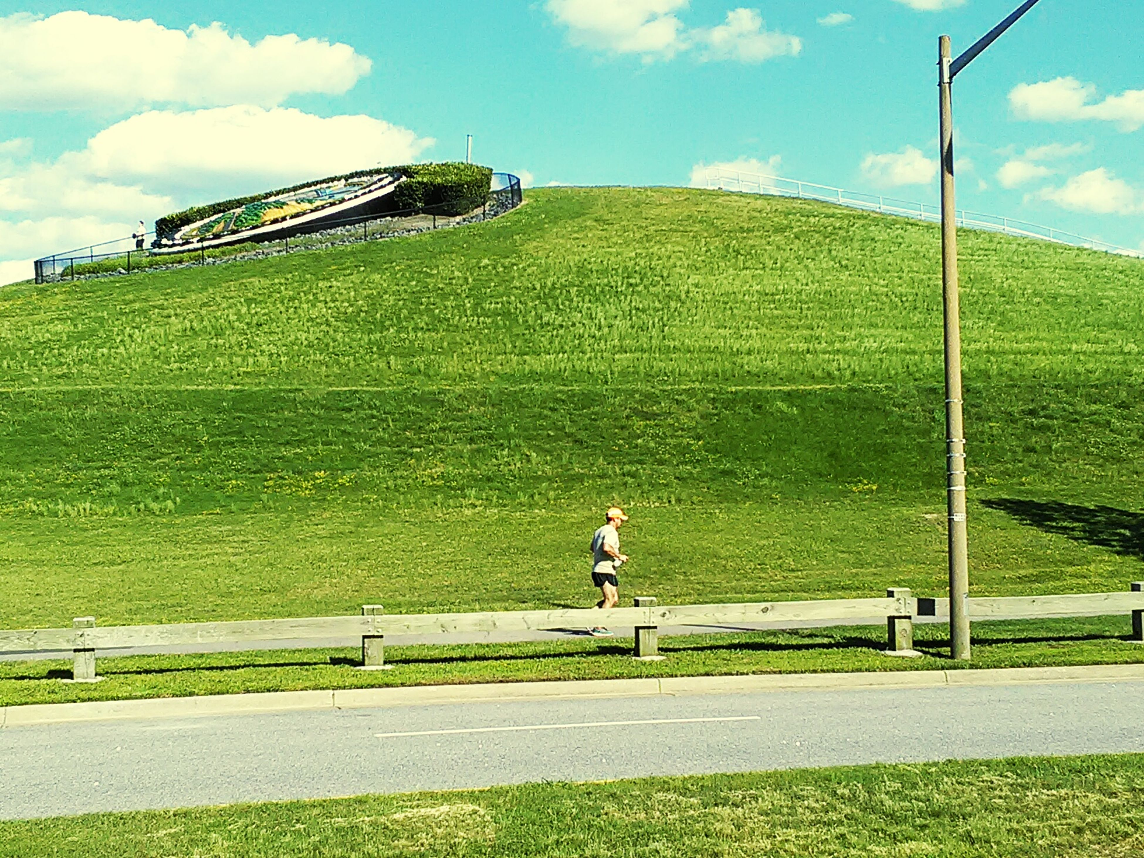 grass, sky, full length, green color, lifestyles, leisure activity, men, cloud - sky, field, sport, grassy, road, rear view, cloud, day, transportation, outdoors, standing