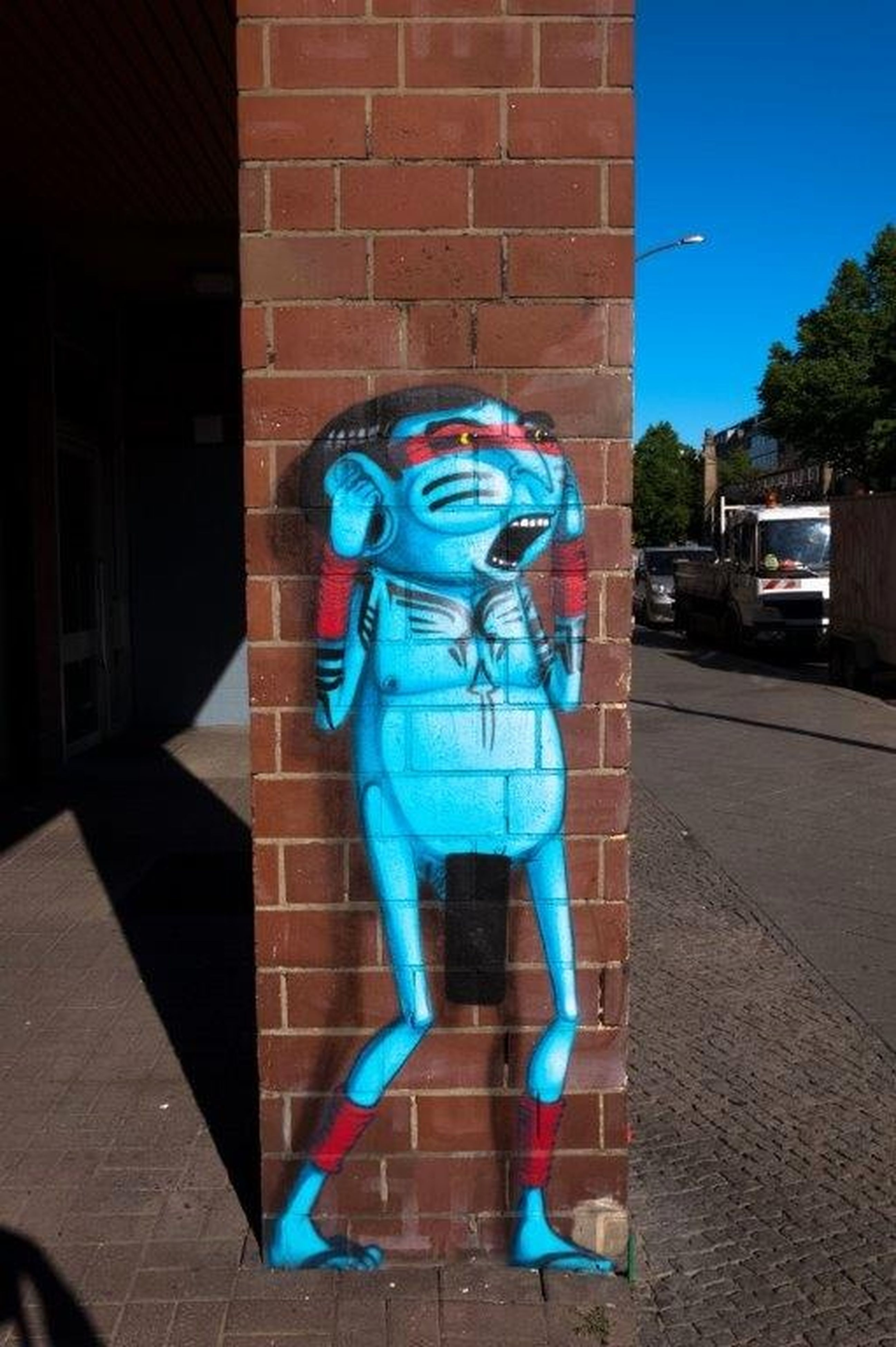 blue, brick wall, bizarre, outdoors, architecture, day, shadow, building exterior, standing, built structure, futuristic, one person, city, full length, sky, people, young adult