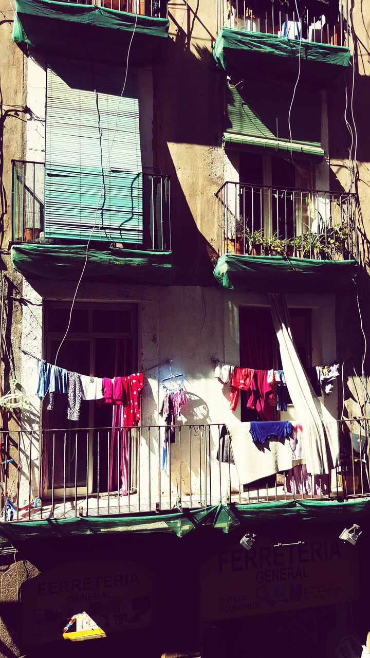 clothesline, architecture, building exterior, drying, built structure, hanging, balcony, laundry, day, clothing, outdoors, real people, working