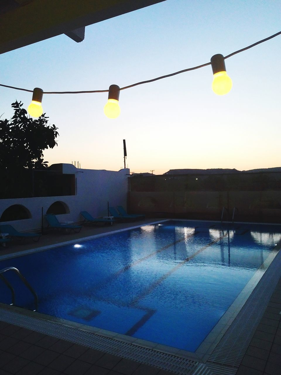 swimming pool, water, no people, outdoors, clear sky, yellow, sunset, tree, day, sky