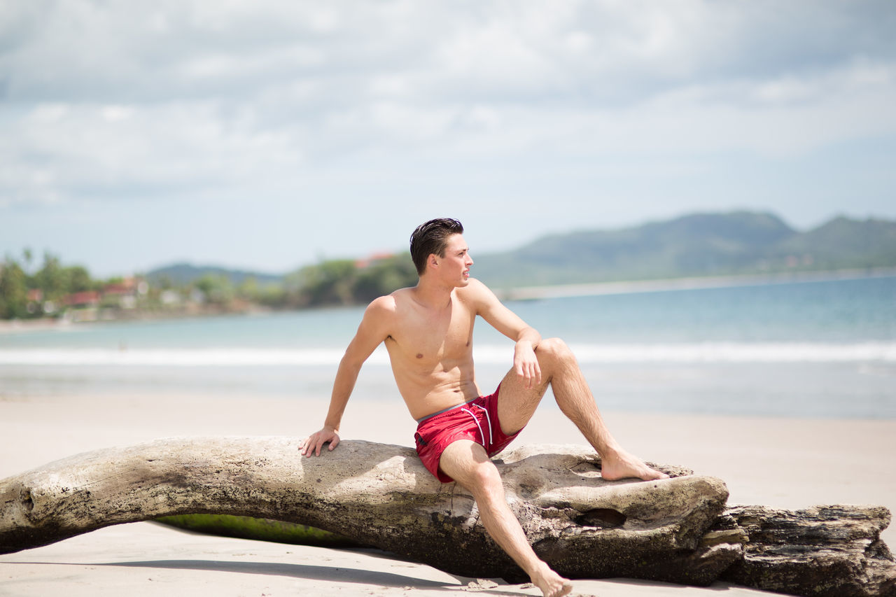 shirtless, water, one person, real people, day, young adult, young men, leisure activity, outdoors, sky, full length, cloud - sky, lifestyles, nature, sea