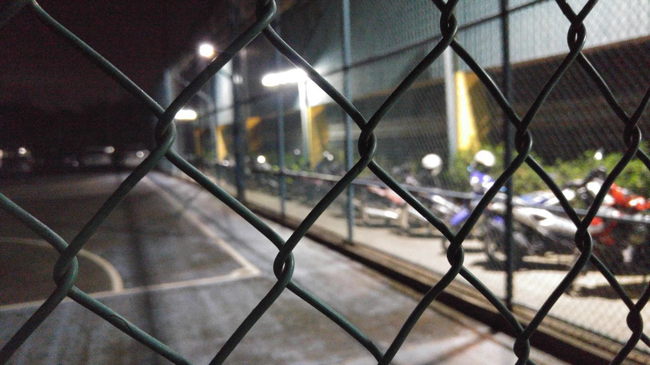 chainlink fence, night, illuminated, no people, protection, architecture, outdoors, built structure, building exterior, close-up, city, sky