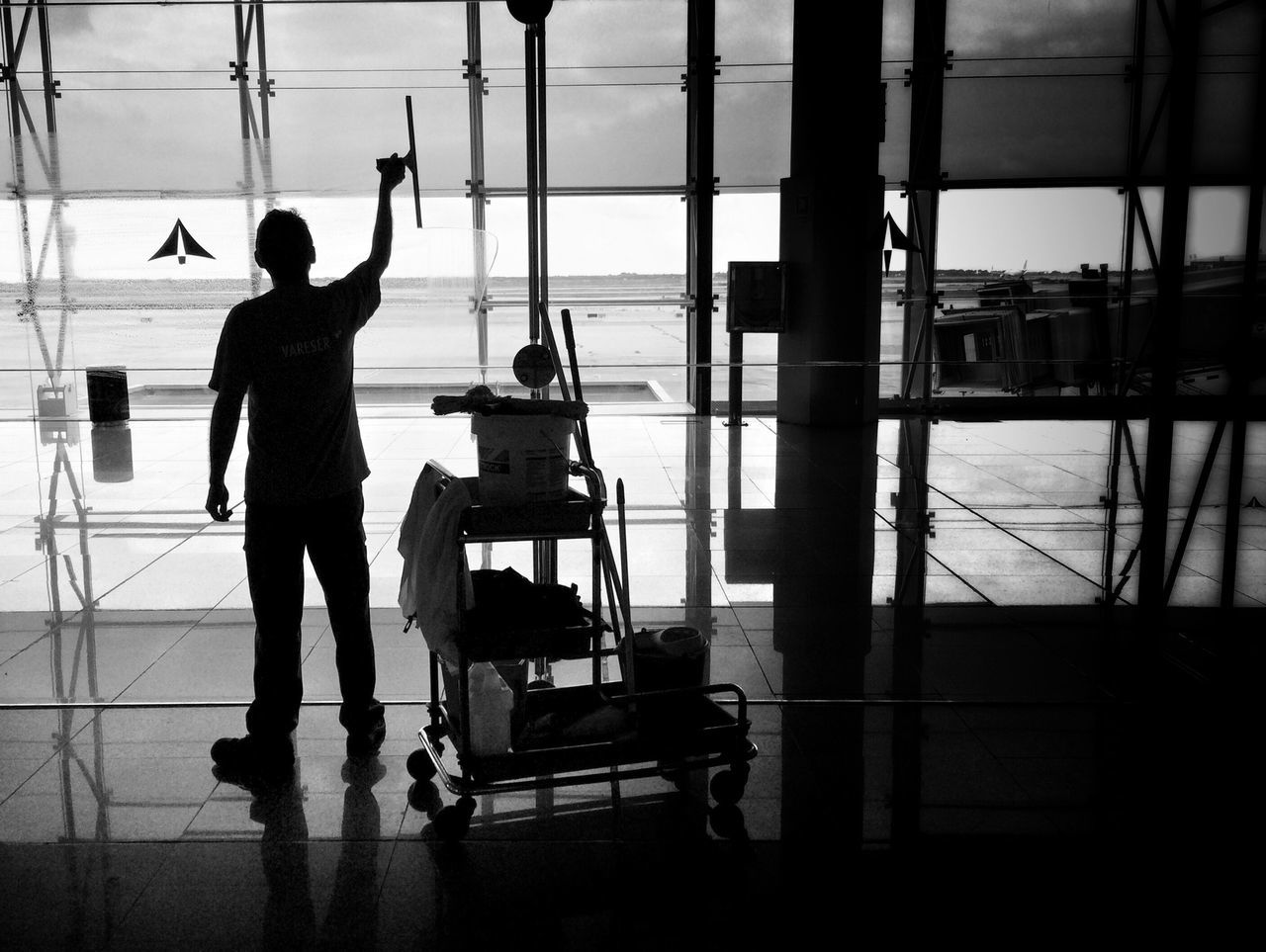 full length, luggage, real people, transportation, silhouette, travel, men, airport, airport departure area, indoors, lifestyles, standing, journey, day, air vehicle, airplane, women, nautical vessel, sky, adult, people