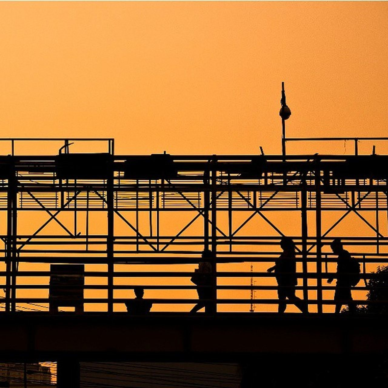 sunset, silhouette, built structure, architecture, clear sky, railing, men, orange color, building exterior, lifestyles, sky, person, copy space, leisure activity, street light, medium group of people, low angle view