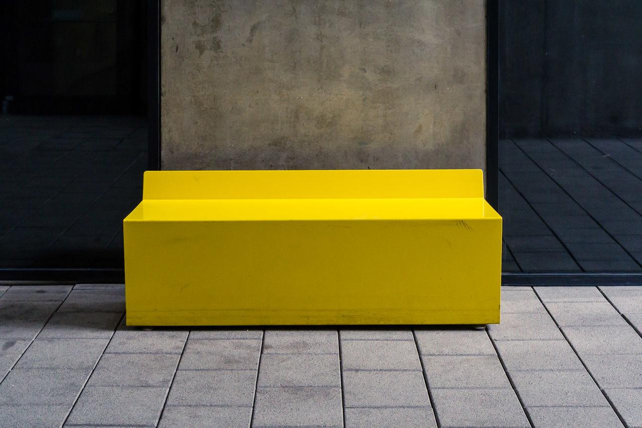 Yellow Seat On Sidewalk In City