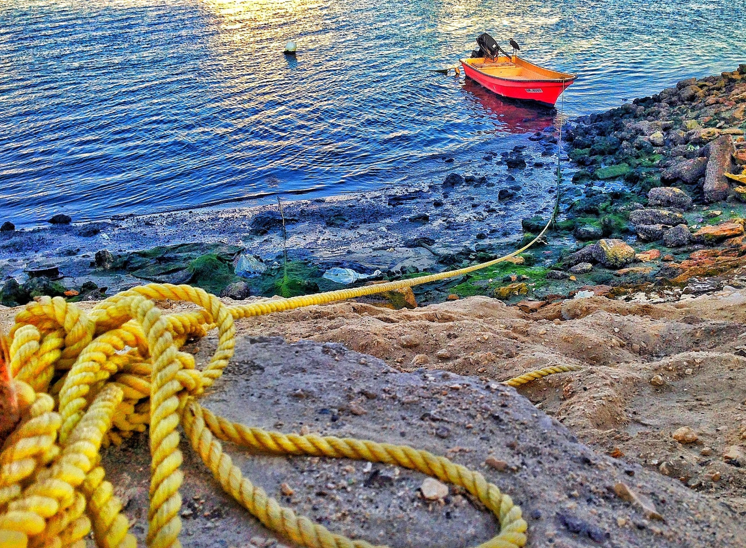 water, transportation, high angle view, mode of transport, yellow, rope, nautical vessel, sea, boat, day, outdoors, no people, fishing industry, rock - object, animal themes, sunlight, nature, tied up, fishing net, moored