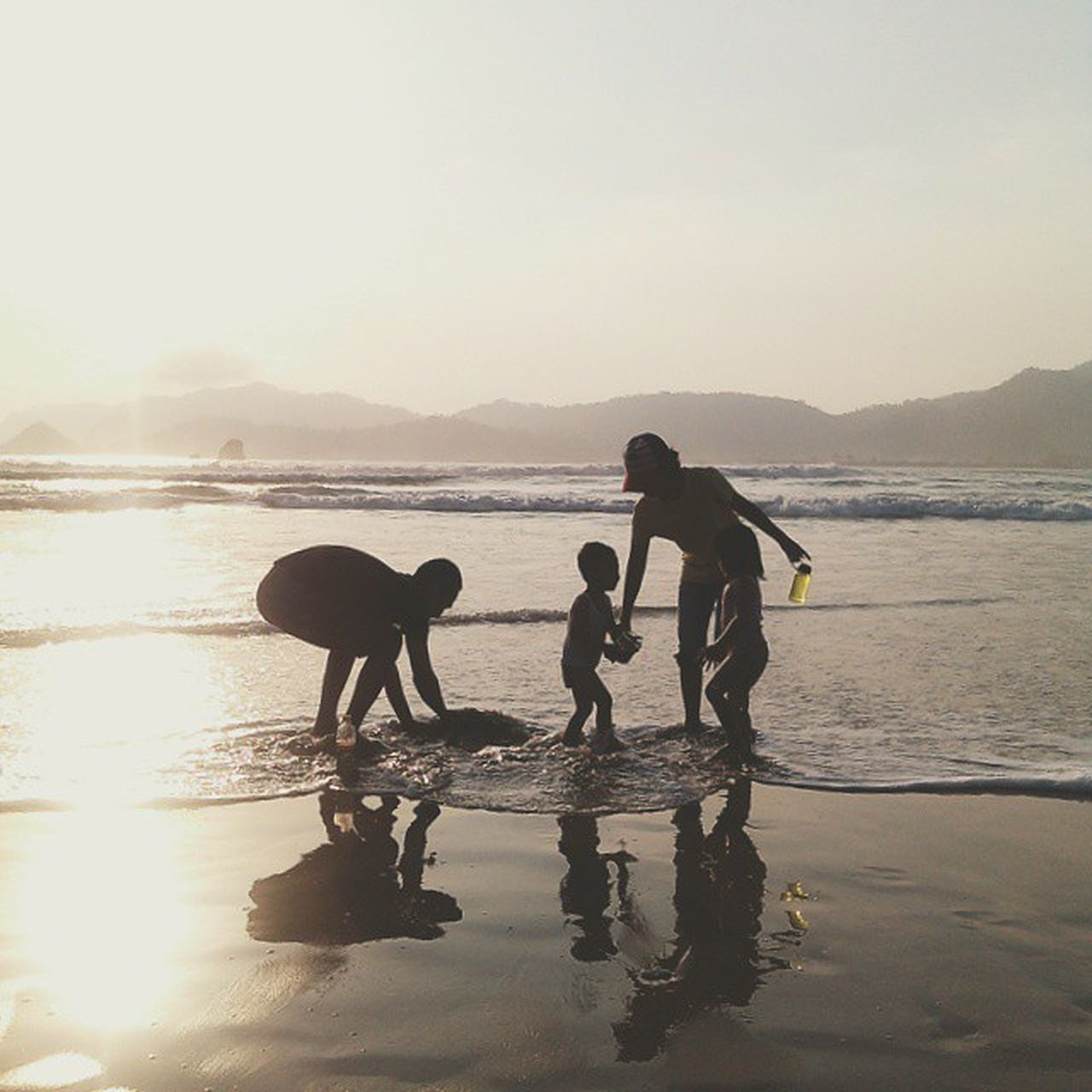 water, real people, silhouette, men, nature, leisure activity, lifestyles, sea, togetherness, two people, outdoors, sky, sunset, full length, beach, scenics, beauty in nature, standing, occupation, friendship, day, extreme sports, people