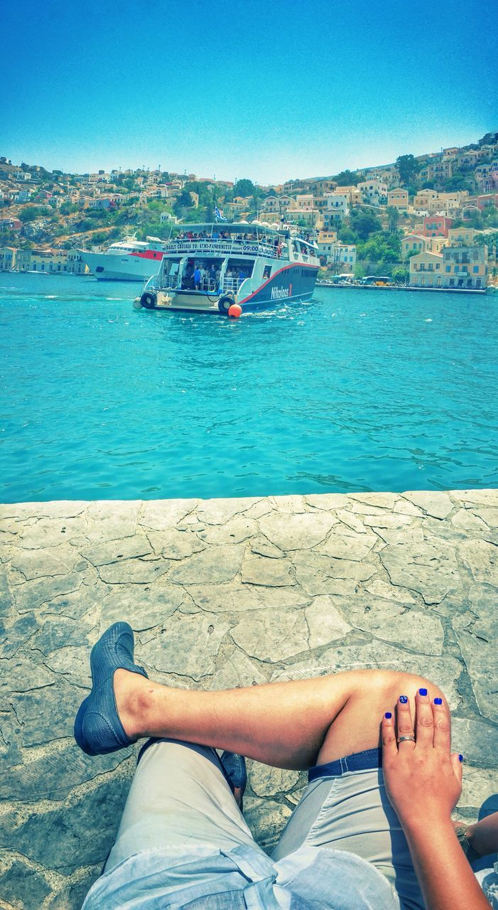 water, low section, human leg, one person, day, barefoot, real people, sitting, sea, clear sky, outdoors, nature, nautical vessel, transportation, women, blue, leisure activity, beauty in nature, lifestyles, scenics, human body part, sky, adult, people