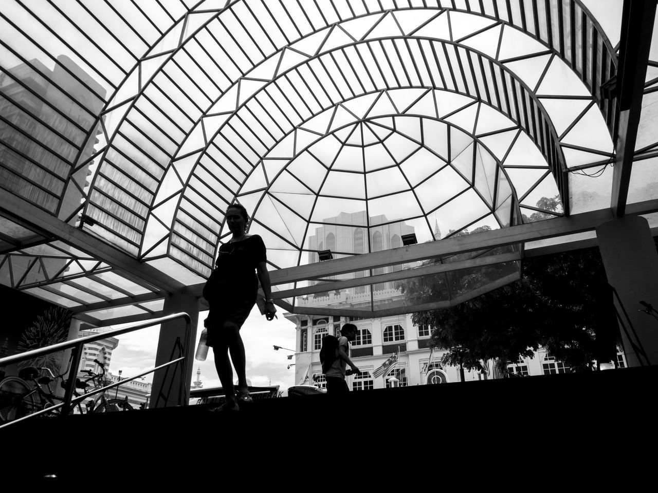 Silhouette of a woman walking down the stairs with a beautiful modern patterned arch above her Arch Architectural Feature B&w B&w Street Photography Black And White Blackandwhite Built Structure City City Life Modern Architecture Patterns Silhouette Streetphotography Urban Urbanphotography