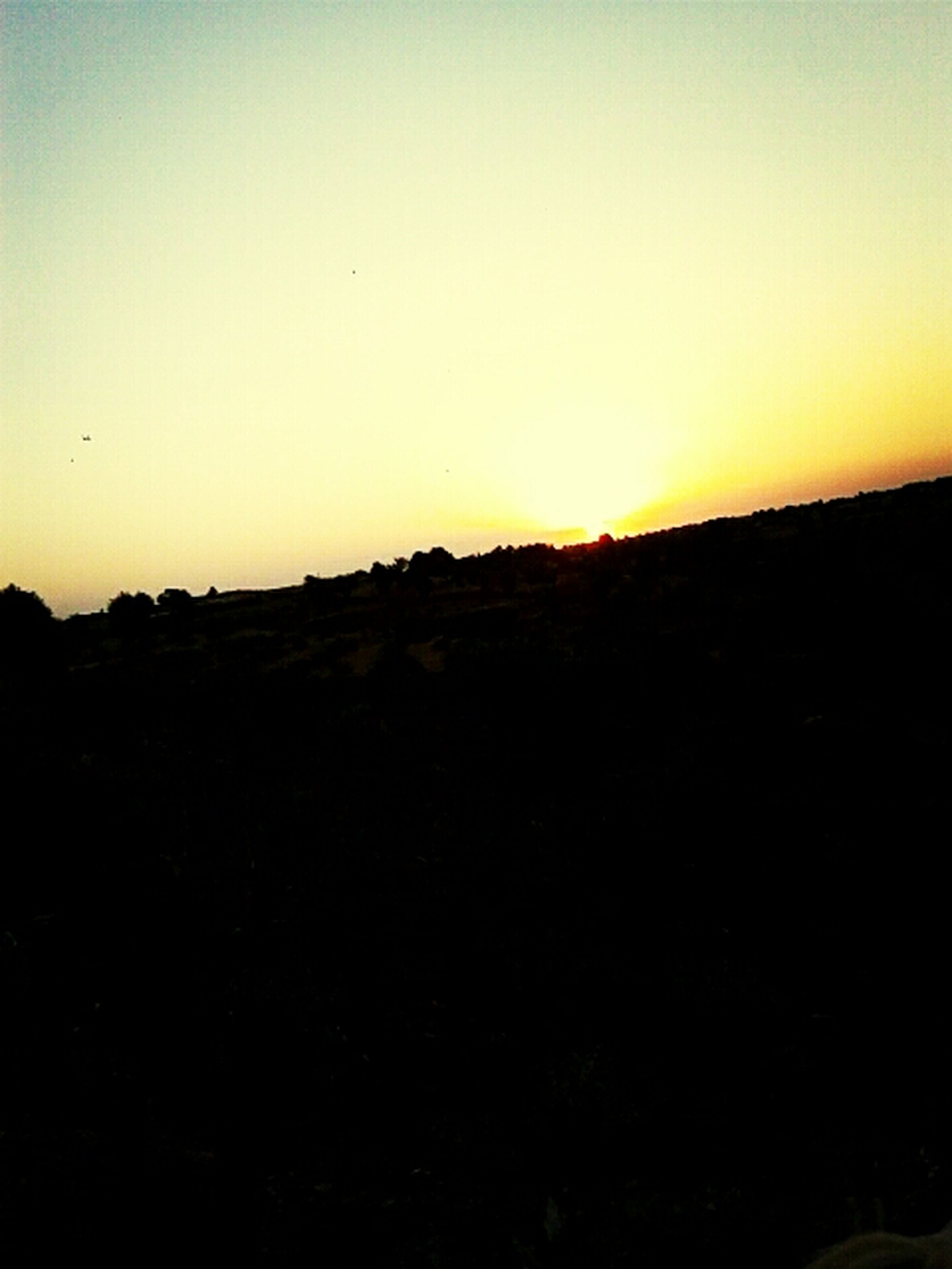 sunset, copy space, silhouette, clear sky, landscape, tranquil scene, scenics, tranquility, beauty in nature, orange color, nature, sky, horizon over land, built structure, dusk, building exterior, dark, field, architecture, idyllic