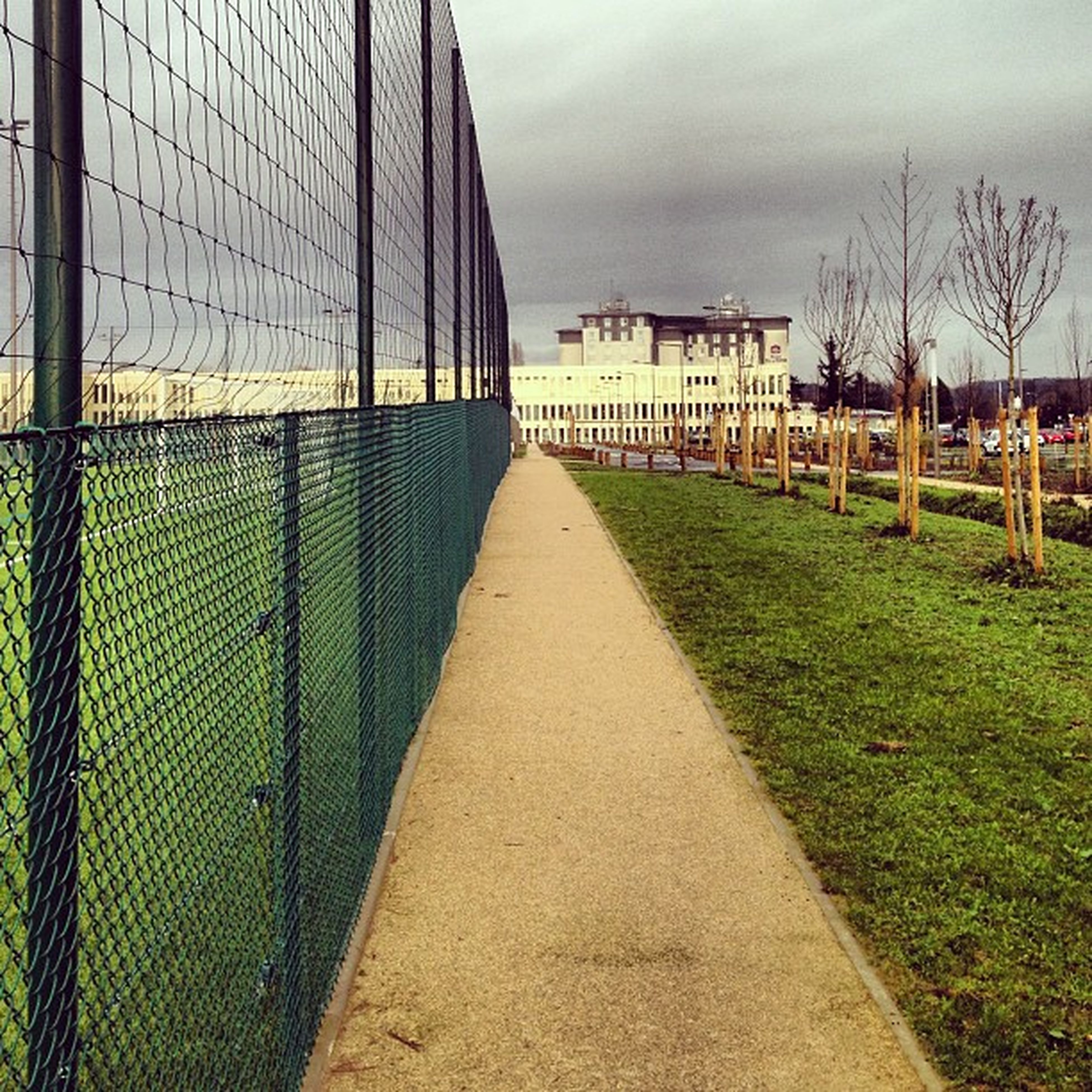 architecture, built structure, the way forward, grass, building exterior, sky, diminishing perspective, vanishing point, fence, walkway, pathway, tree, cloud - sky, footpath, railing, empty, day, outdoors, no people, cloud