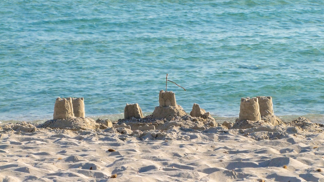 Scenic View Of Sand Castle Against Sea