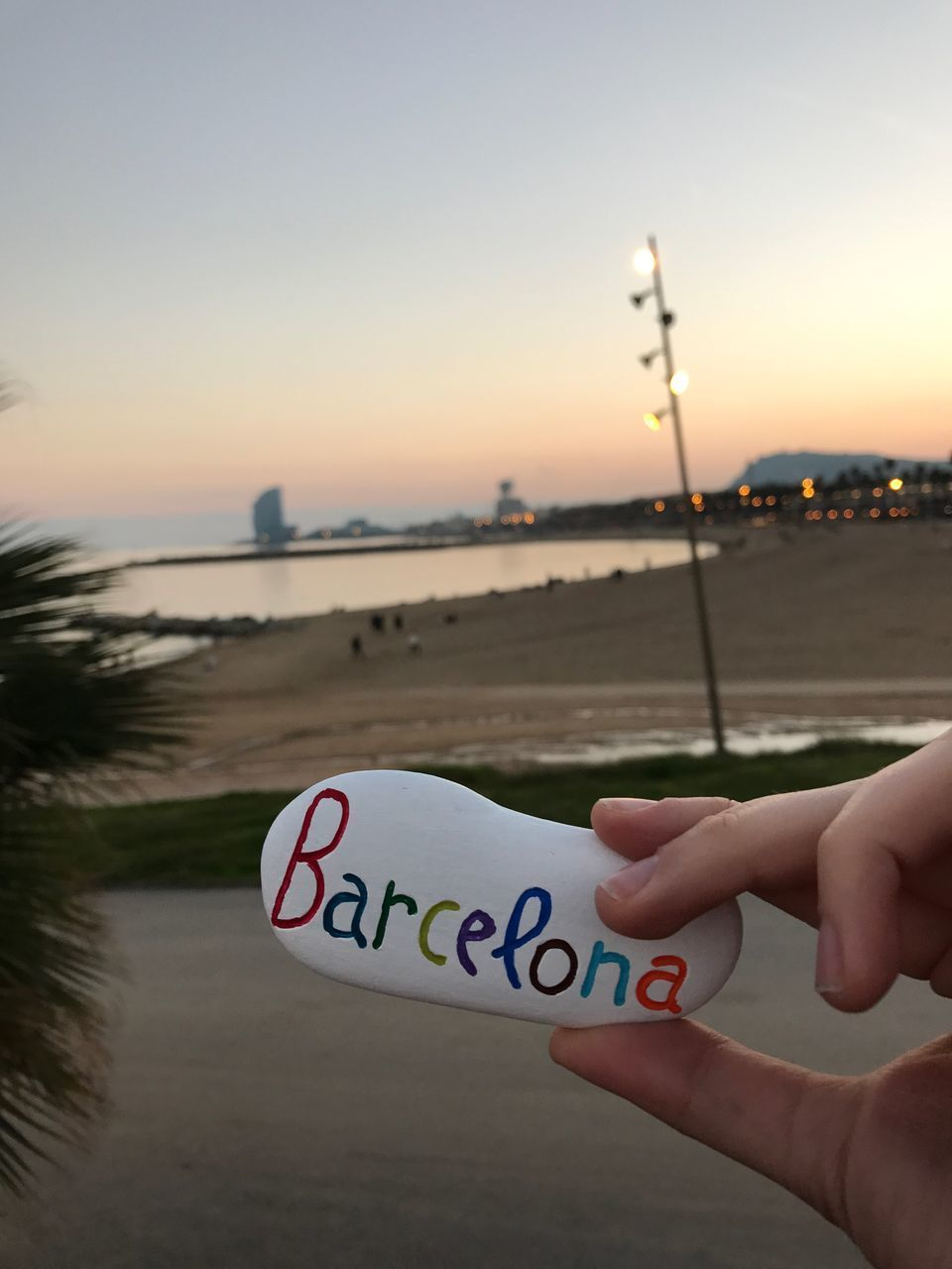 human hand, human body part, one person, text, communication, sunset, human finger, holding, real people, outdoors, sky, close-up, nature, water, beauty in nature, clear sky, day, people
