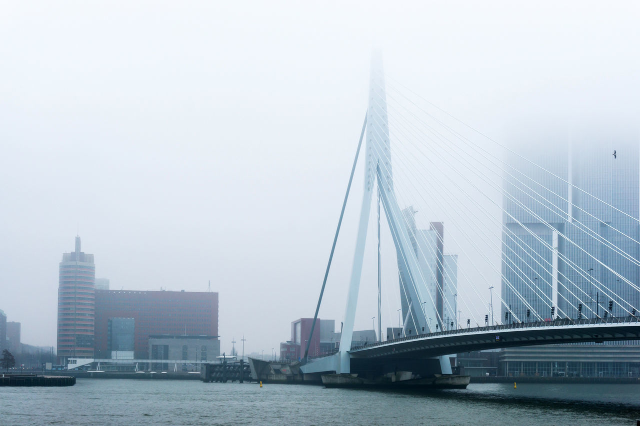 Architecture Bridge - Man Made Structure Building Exterior Built Structure City Cityscape Connection Day Downtown District Fog Modern No People Outdoors River Sky Skyscraper Suspension Bridge Transportation Urban Skyline Water