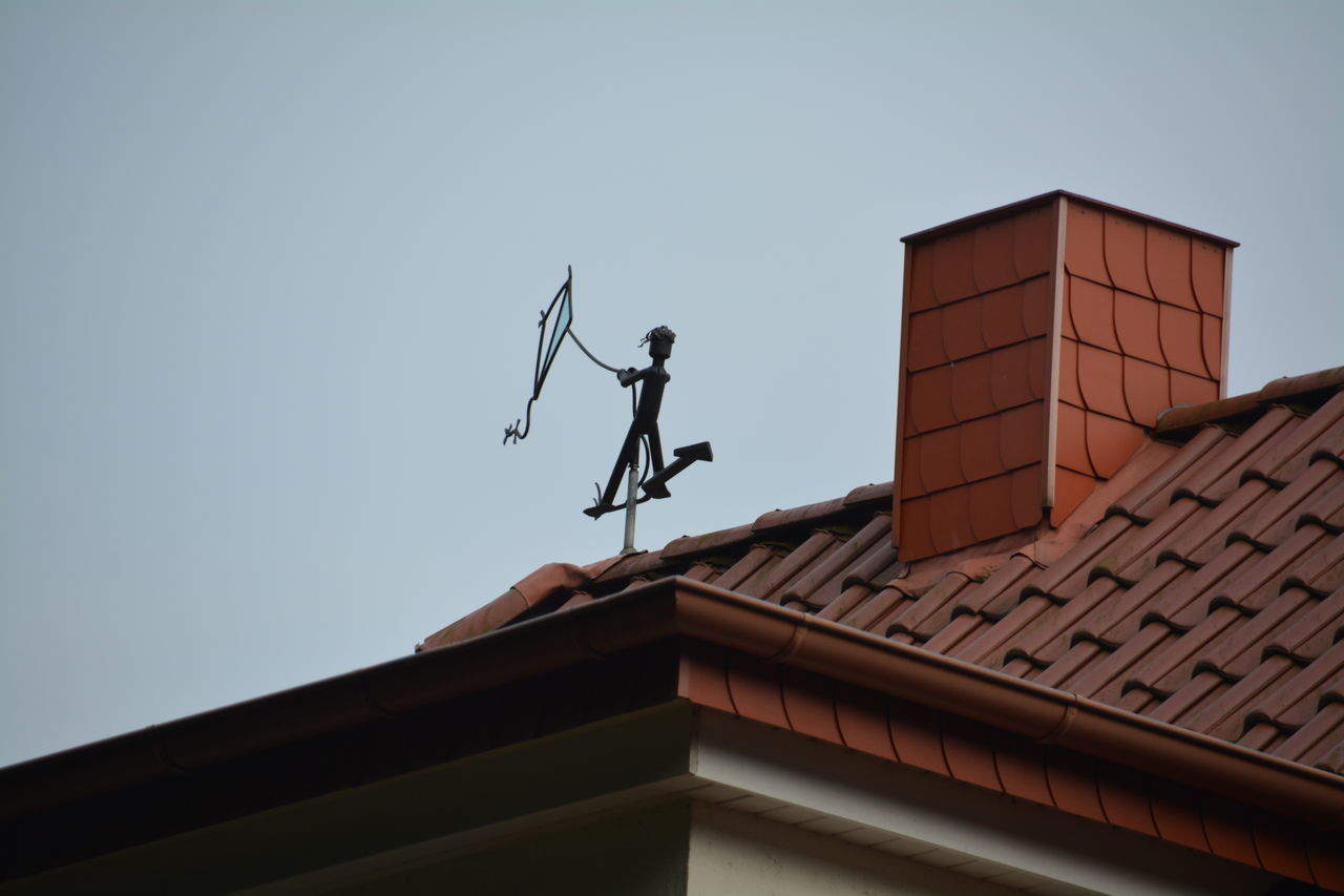 Low Angle View Of Antenna On House Roof