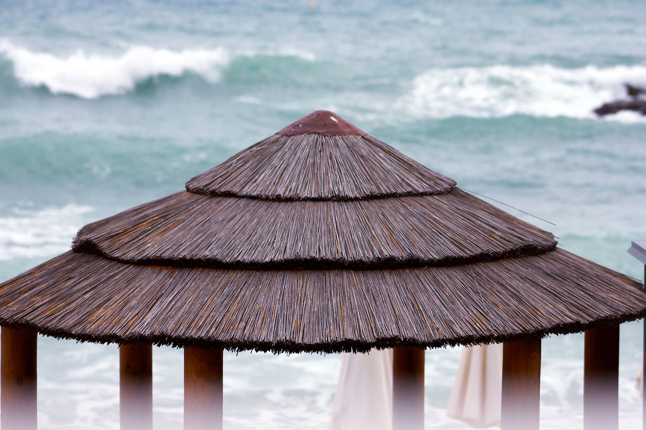 water, thatched roof, sea, day, wood - material, roof, beach, focus on foreground, nature, no people, outdoors, tranquility, beauty in nature, close-up