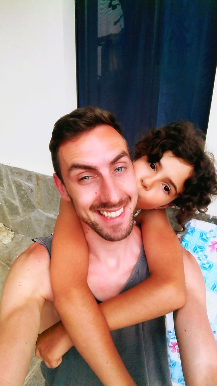 shirtless, looking at camera, togetherness, leisure activity, real people, portrait, love, lifestyles, father, indoors, bonding, smiling, childhood, young men, family with one child, young adult, happiness, men, day, young women, close-up, people