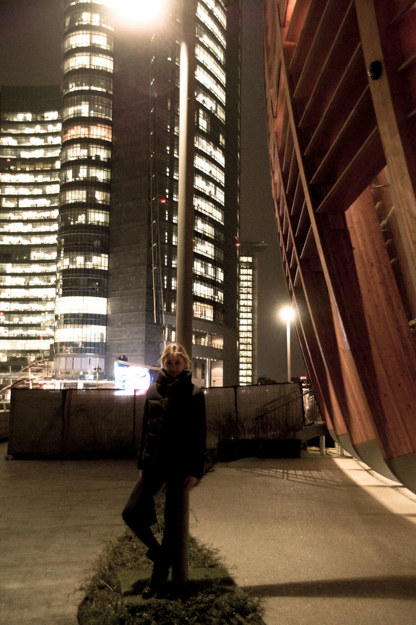 illuminated, real people, one person, night, built structure, full length, architecture, standing, men, indoors, lifestyles, building exterior, skyscraper, city, occupation, young adult, adult, people