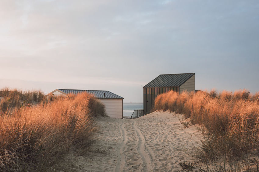 Dune path to the beach Architecture Beach Beach House Beauty In Nature Building Exterior Built Structure Cold Temperature Day Grass Marram Grass Nature No People Outdoors Resort Sand Sand Dune Scenics Sky Tranquility Water