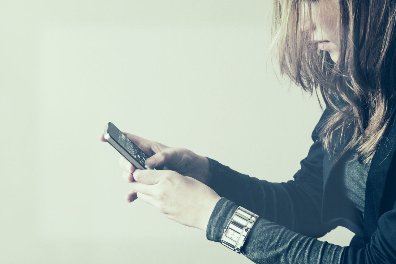 Side View Of Woman Using Smart Phone Against Wall