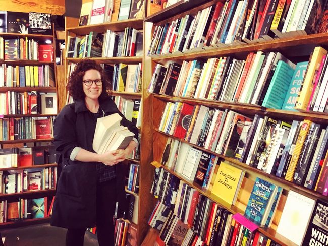 Looking At Camera Portrait Smiling Bookshelf Shelf One Person Book One Woman Only Choice Only Women Library Large Group Of Objects Adults Only Retail  Store Bookstore Standing Happiness Young Adult Business