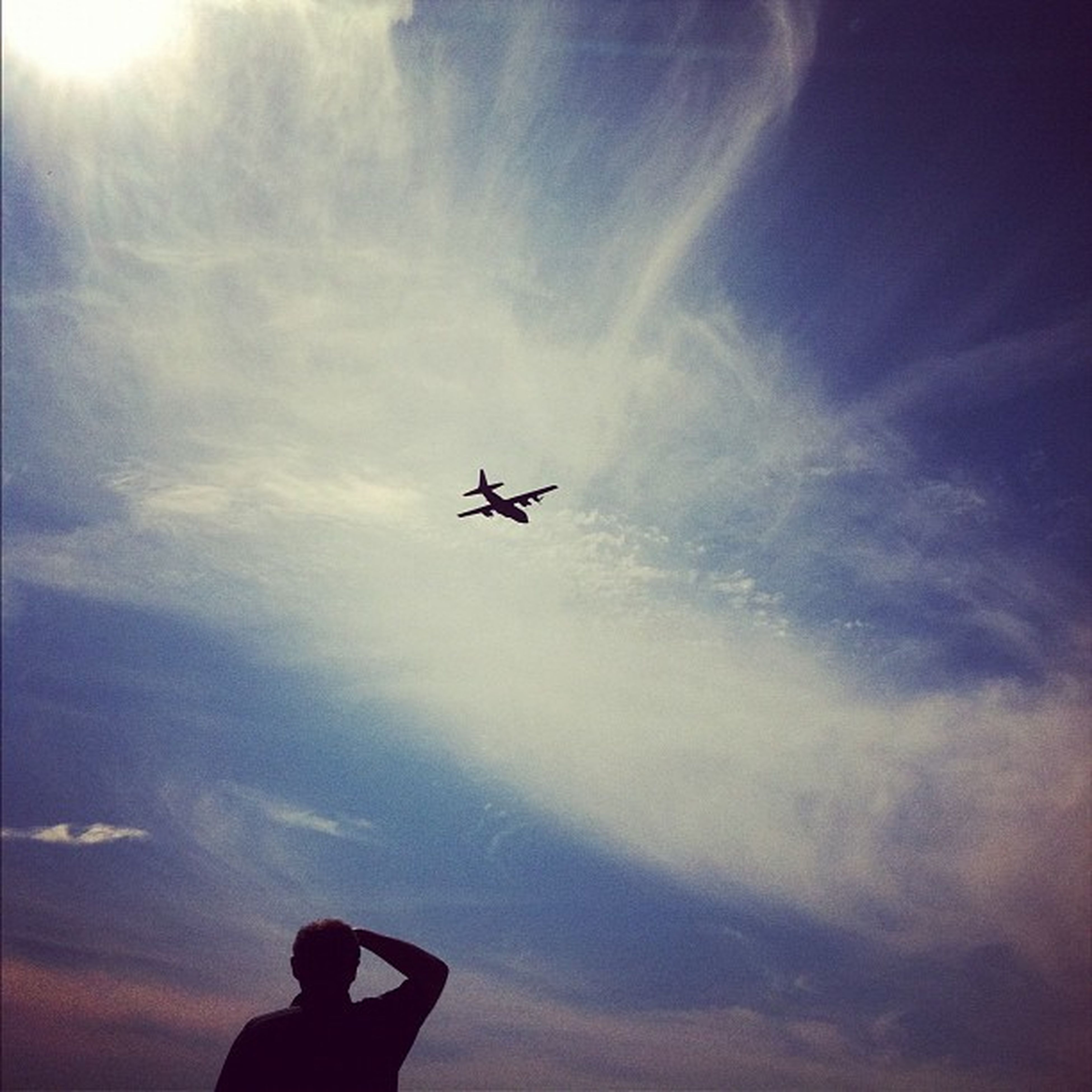 transportation, low angle view, airplane, sky, silhouette, air vehicle, mode of transport, lifestyles, leisure activity, cloud - sky, flying, mid-air, men, journey, travel, unrecognizable person, on the move, cloud