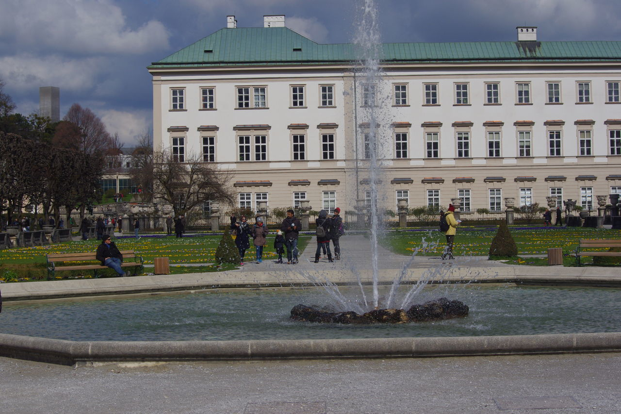 architecture, building exterior, built structure, real people, water, large group of people, day, men, women, lifestyles, outdoors, spraying, sky, city, tree, nature, people