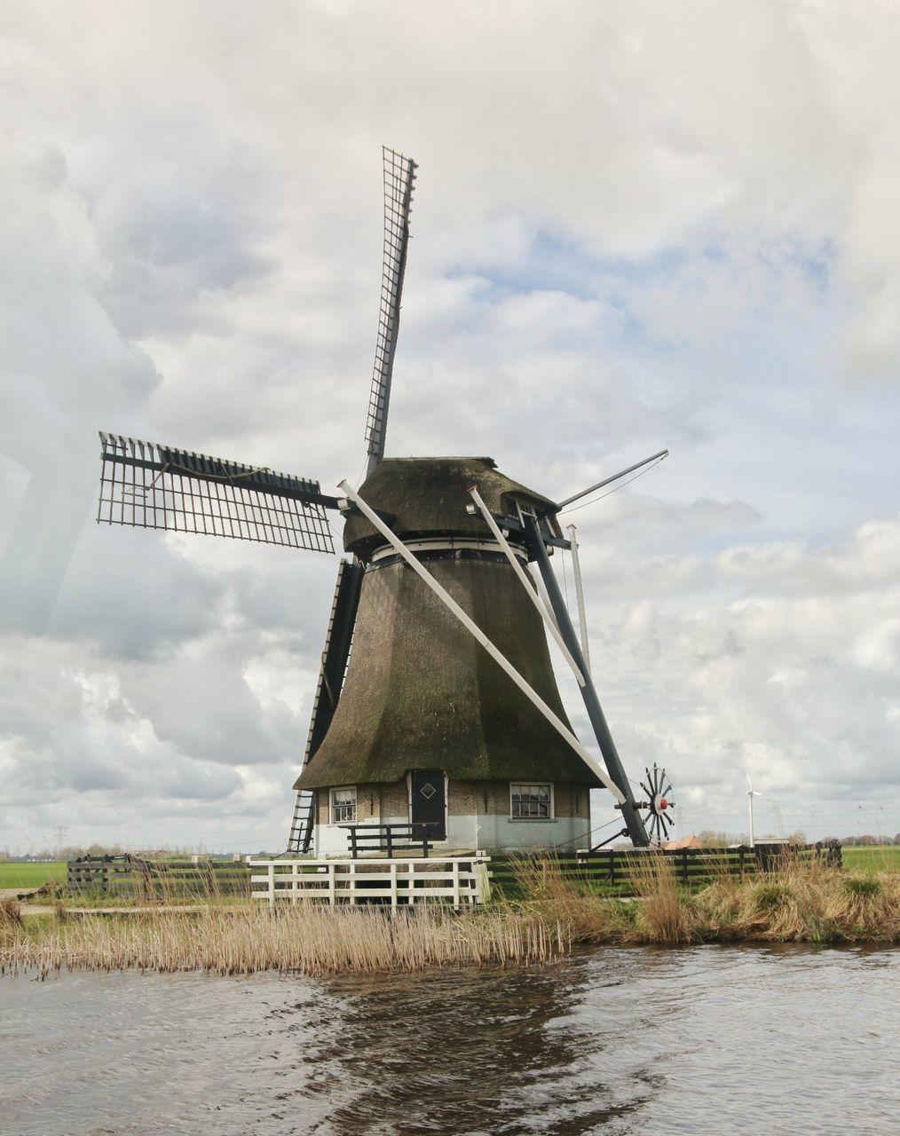alternative energy, wind power, windmill, wind turbine, environmental conservation, renewable energy, cloud - sky, fuel and power generation, traditional windmill, sky, industrial windmill, water, day, outdoors, built structure, architecture, nature, field, waterfront, no people, rural scene, building exterior, technology, beauty in nature