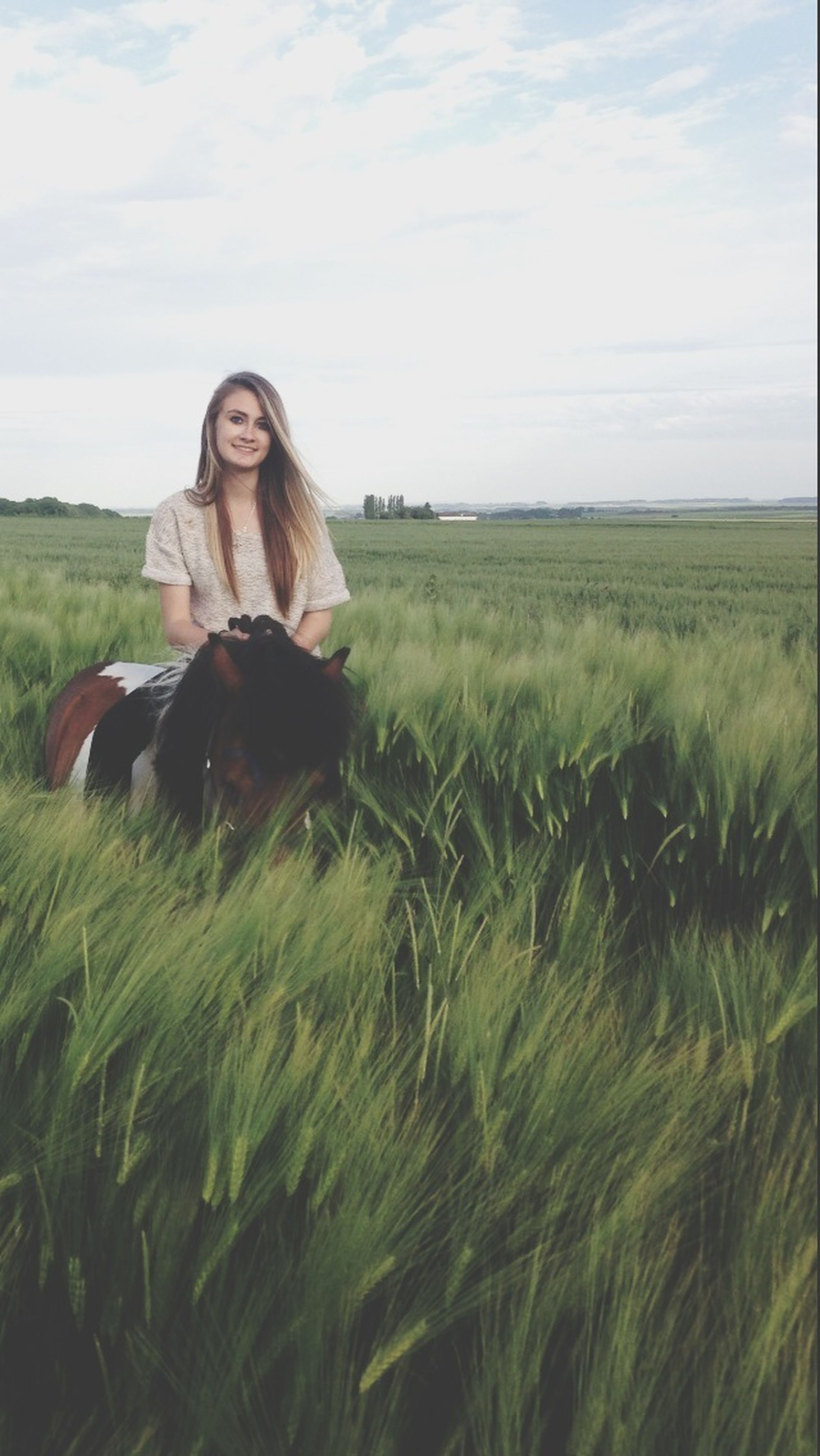 field, grass, landscape, sky, rural scene, young adult, agriculture, tranquility, tranquil scene, grassy, nature, growth, young women, farm, person, plant, beauty in nature, standing