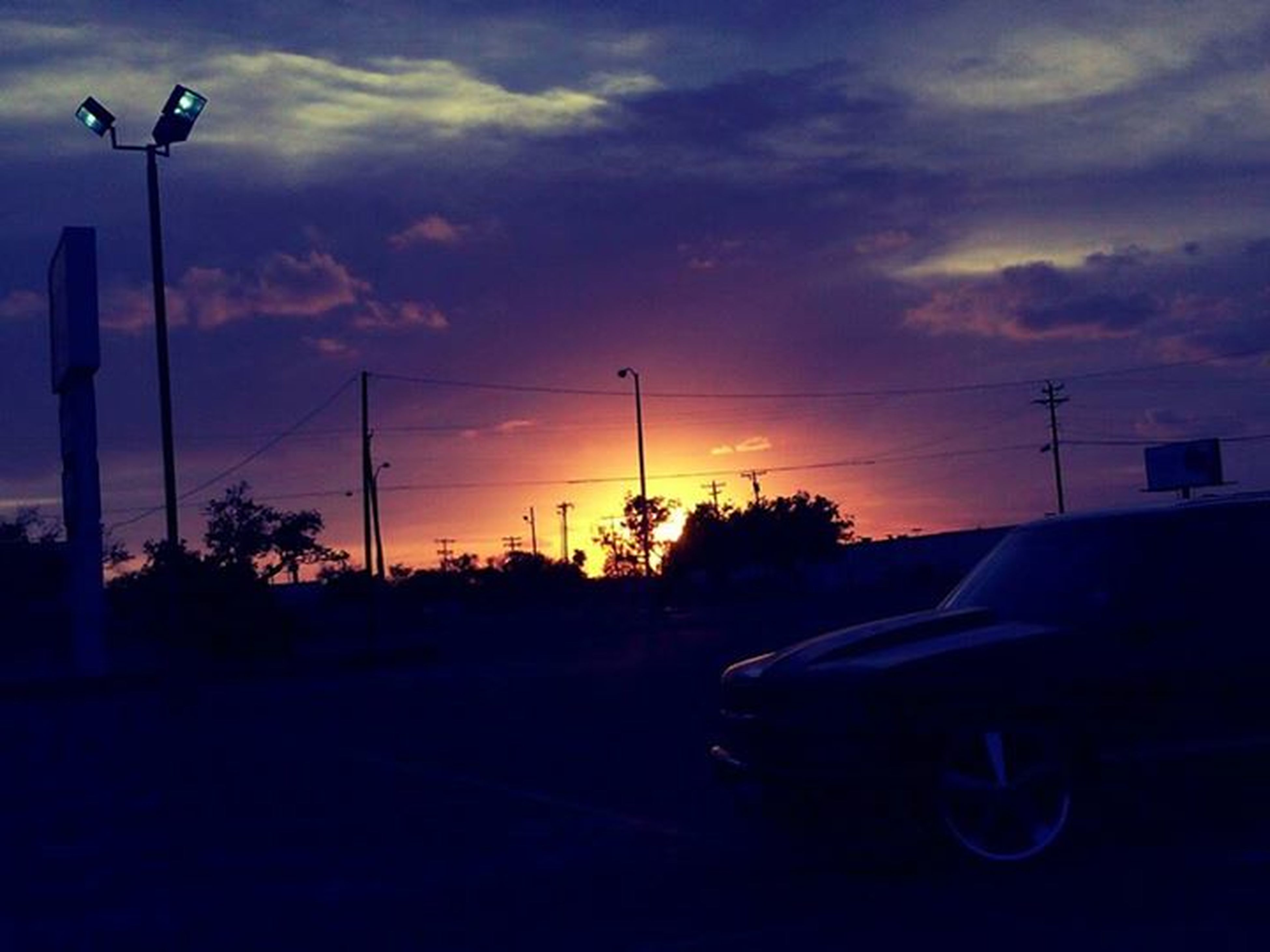 sunset, sky, silhouette, street light, orange color, cloud - sky, transportation, beauty in nature, nature, scenics, tranquility, cloud, car, dusk, lighting equipment, tree, tranquil scene, no people, land vehicle, outdoors