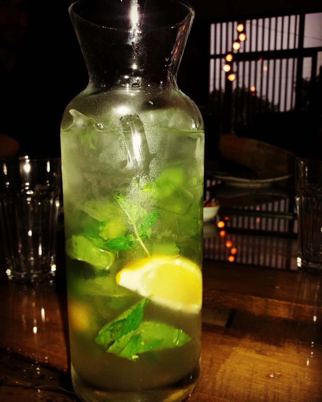 drink, refreshment, table, drinking glass, bottle, indoors, green color, alcohol, food and drink, no people, cocktail, freshness, close-up, liquid, mint leaf - culinary, mojito, night, liqueur