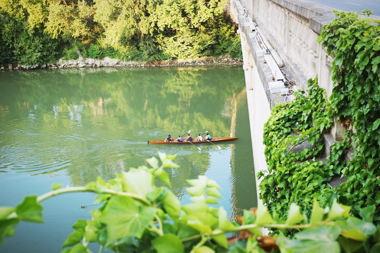 High Angle View Of People Kayaking On River Under Bridge
