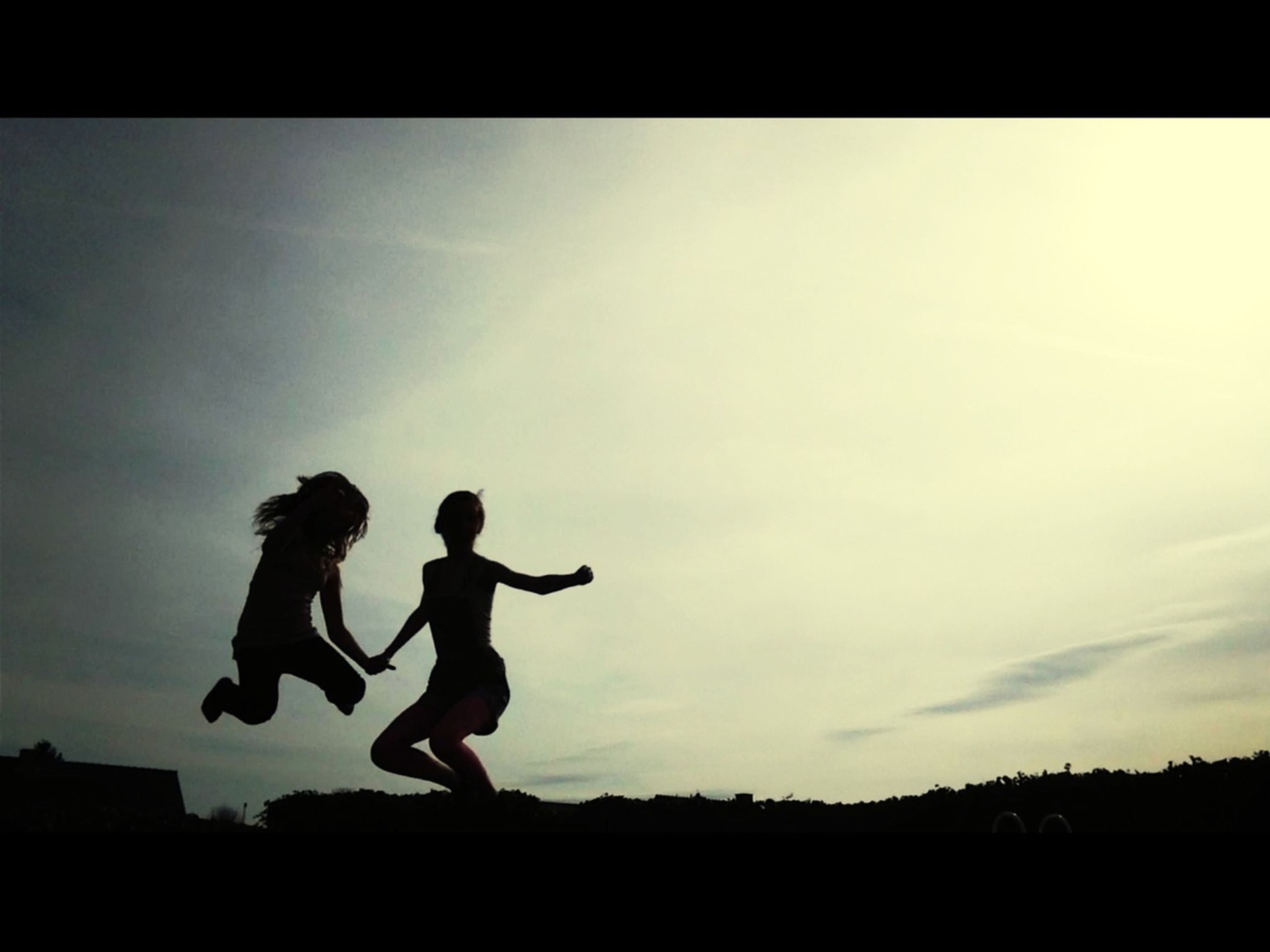 silhouette, full length, sky, lifestyles, leisure activity, transfer print, men, auto post production filter, low angle view, cloud - sky, standing, side view, copy space, childhood, enjoyment, mid-air, arms raised, dusk